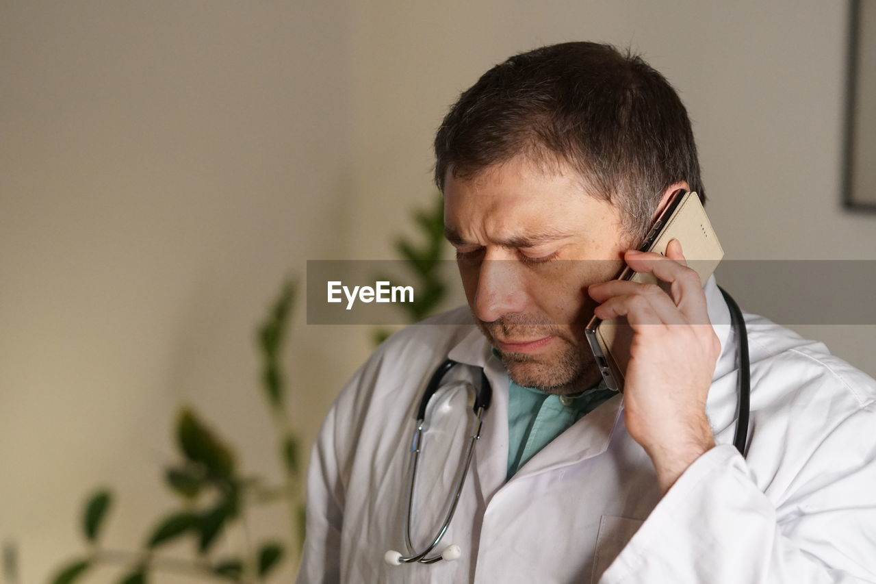 Close-Up Of Mature Doctor Using Phone Against Wall