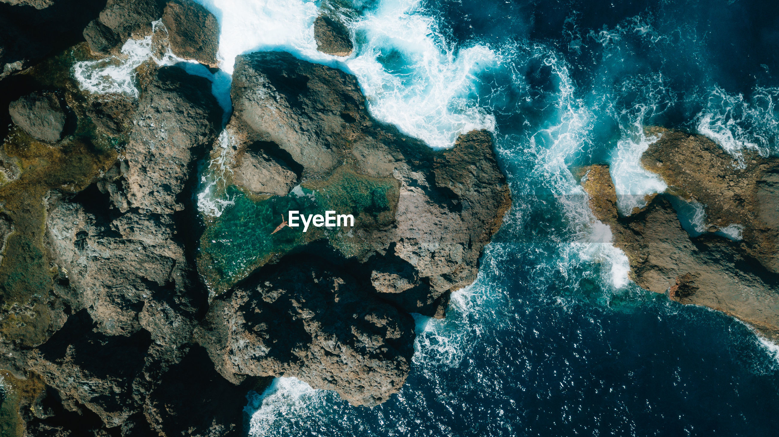 Aerial view of woman swimming in water amidst rock formation in sea
