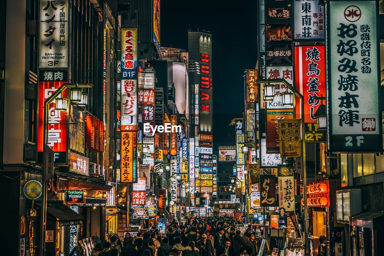 advertisement, text, night, communication, illuminated, city, building exterior, architecture, neon, large group of people, travel destinations, built structure, outdoors, crowd, people