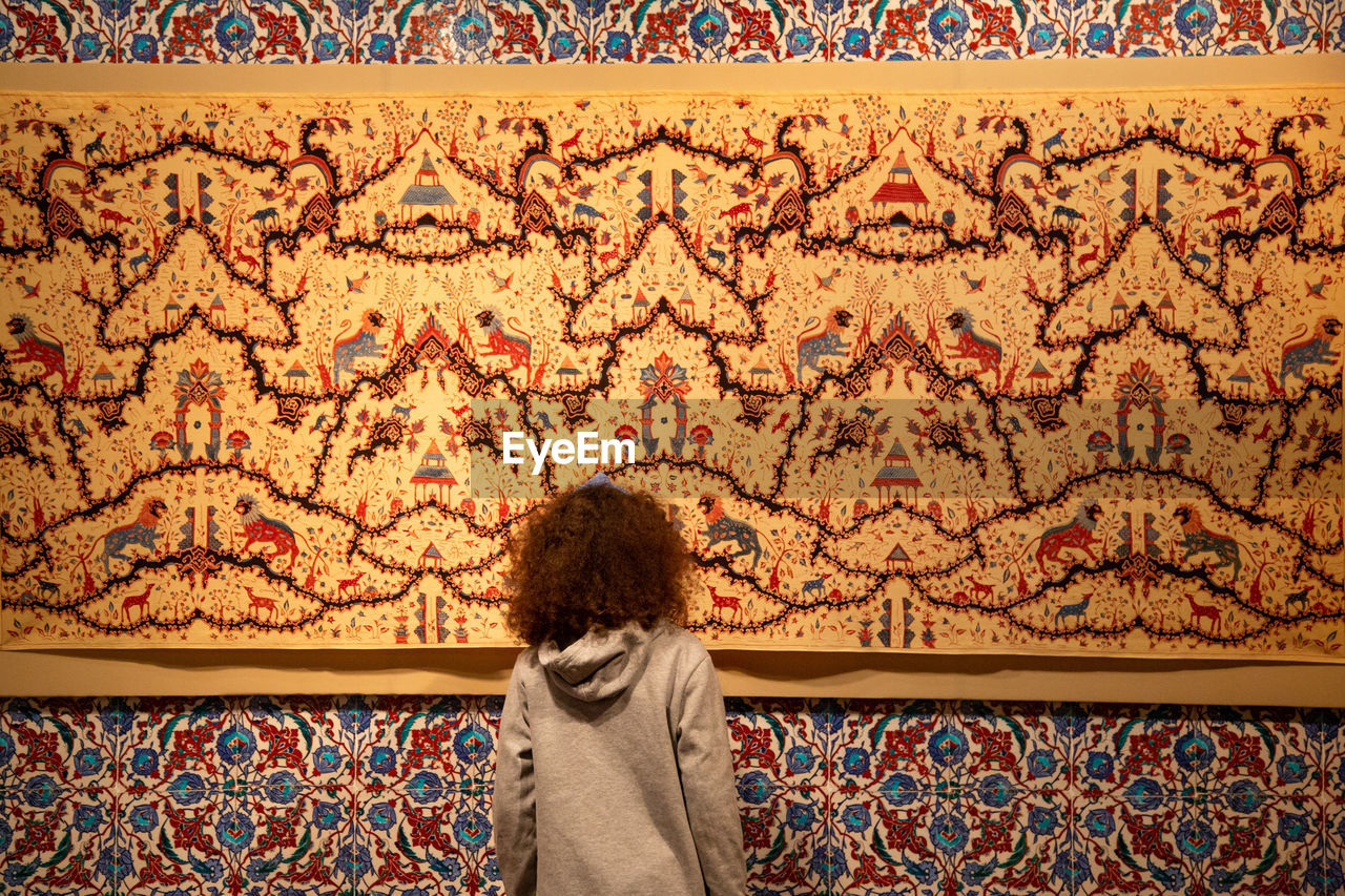 one person, architecture, pattern, creativity, wall - building feature, rear view, art and craft, indoors, standing, floral pattern, women, looking, day, multi colored, mural, carpet - decor, adult, wallpaper, wall