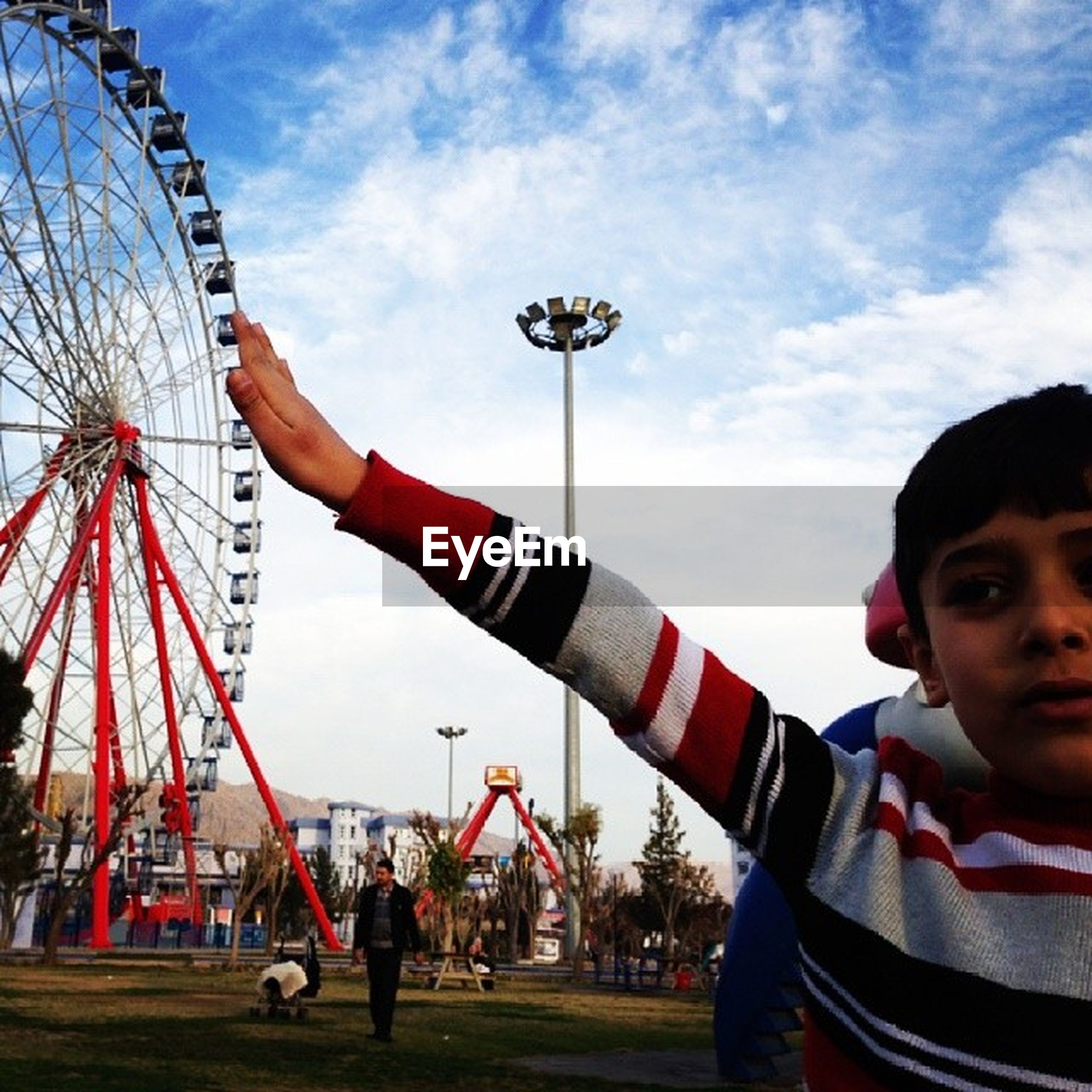 amusement park, amusement park ride, leisure activity, lifestyles, arts culture and entertainment, ferris wheel, sky, architecture, built structure, cloud - sky, fun, men, travel, person, travel destinations, casual clothing, tourism, enjoyment