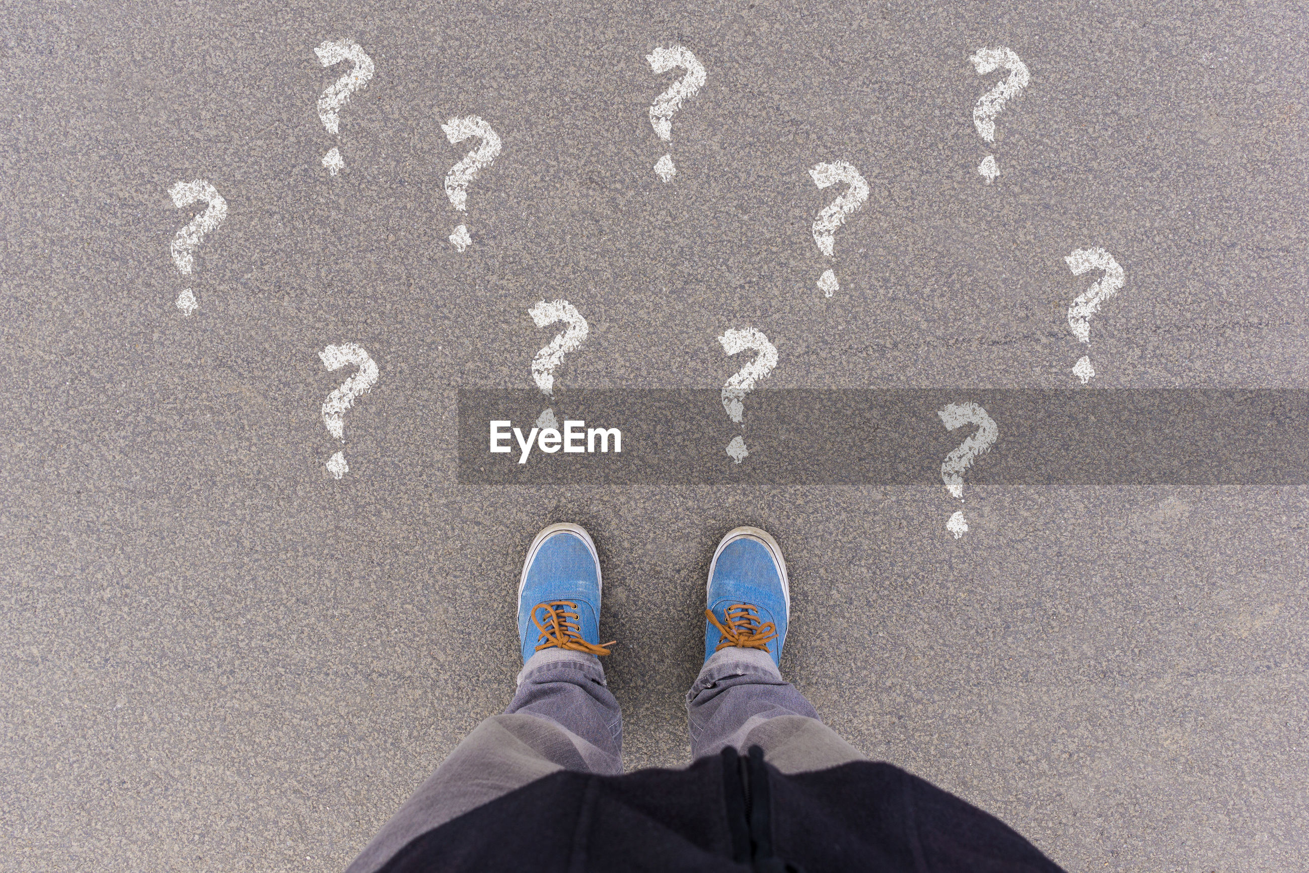 Low section of man standing by question marks on road