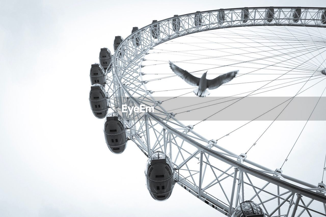 low angle view, amusement park, day, sky, outdoors, flying, no people, amusement park ride, animal themes, spread wings, nature
