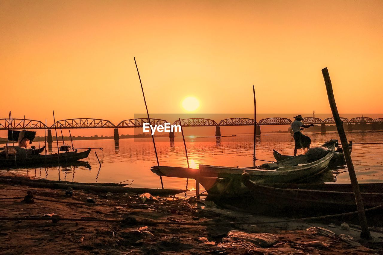 water, sunset, sky, nautical vessel, orange color, transportation, mode of transportation, sun, real people, beauty in nature, moored, nature, one person, sea, scenics - nature, beach, silhouette, tranquility, tranquil scene, outdoors, fishing boat