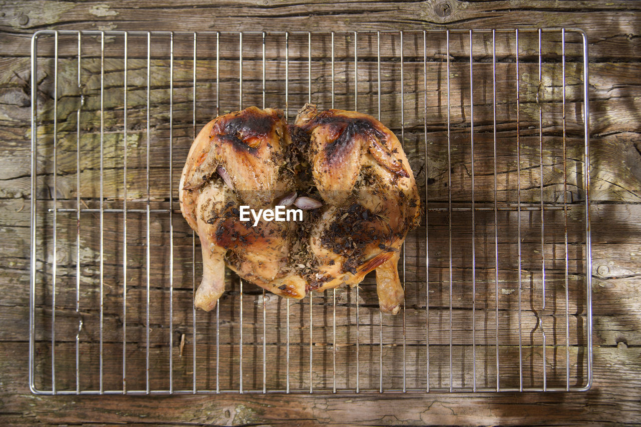 Directly above shot of roast chicken on rack over wooden table