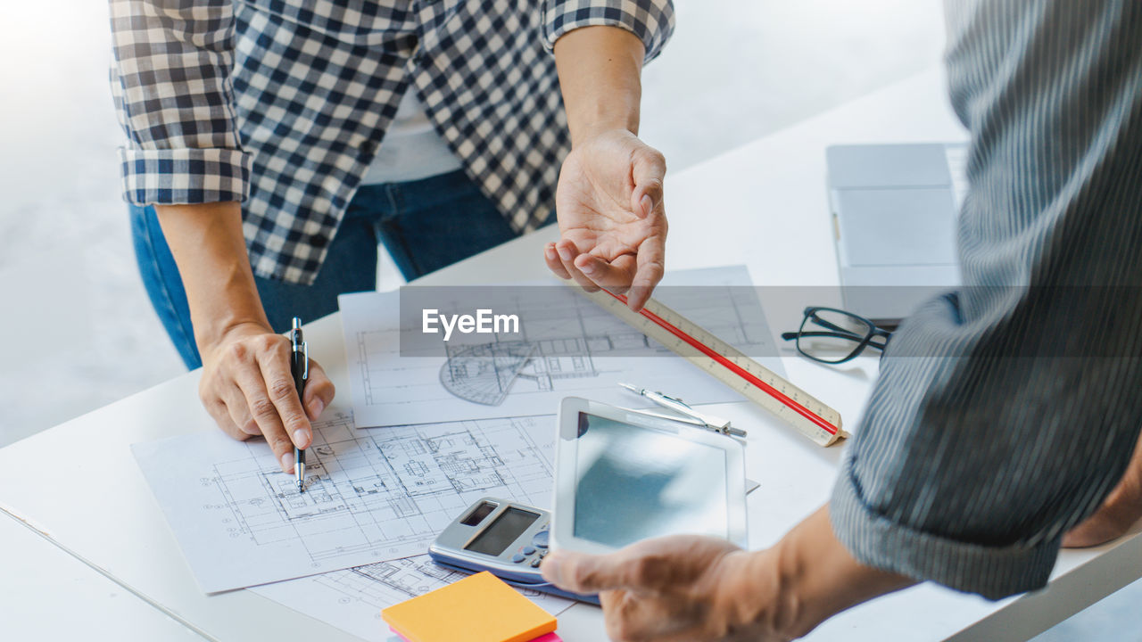 Midsection of architects working on plans at office