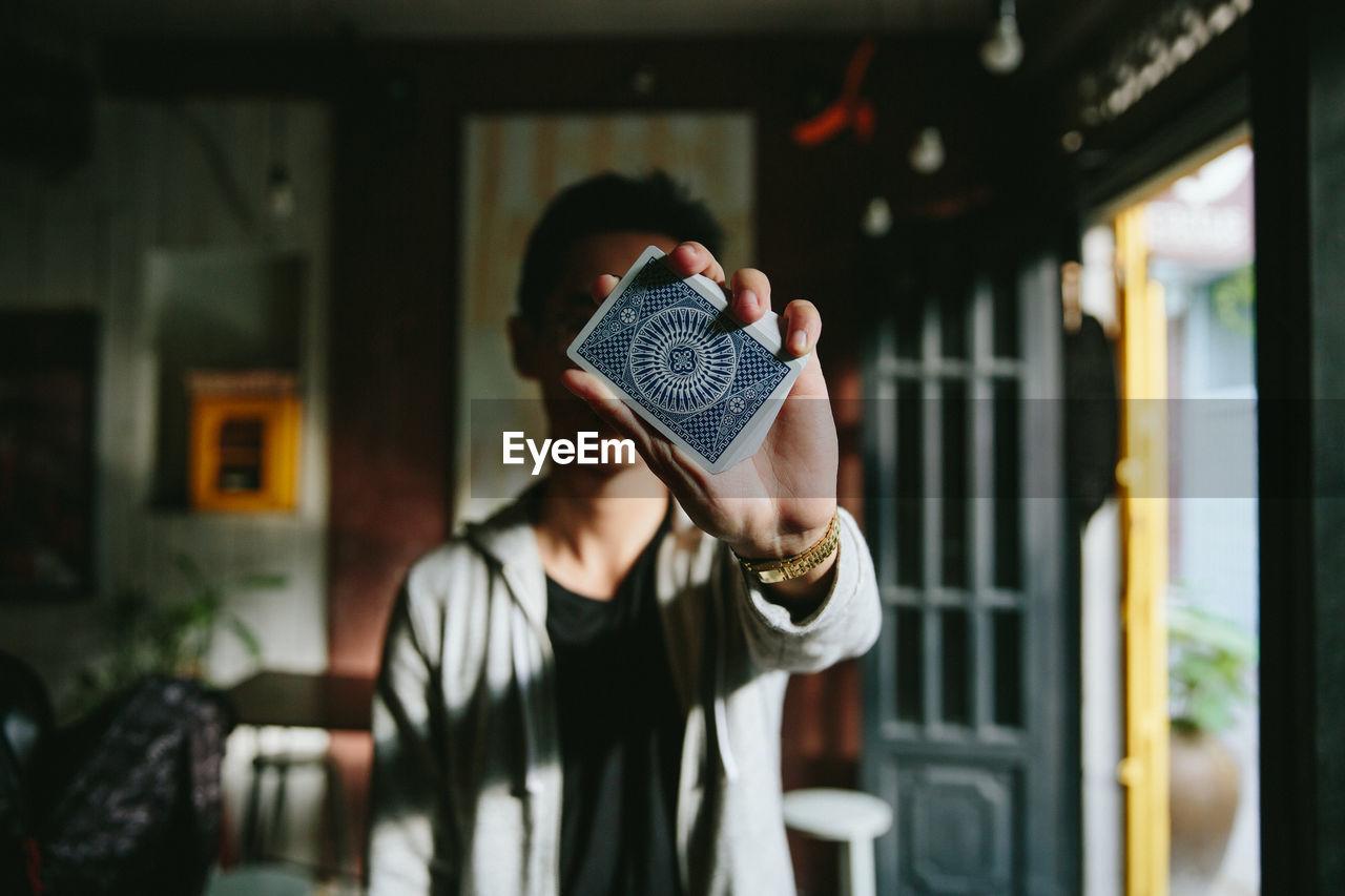 Man Holding Up A Card Towards Camera