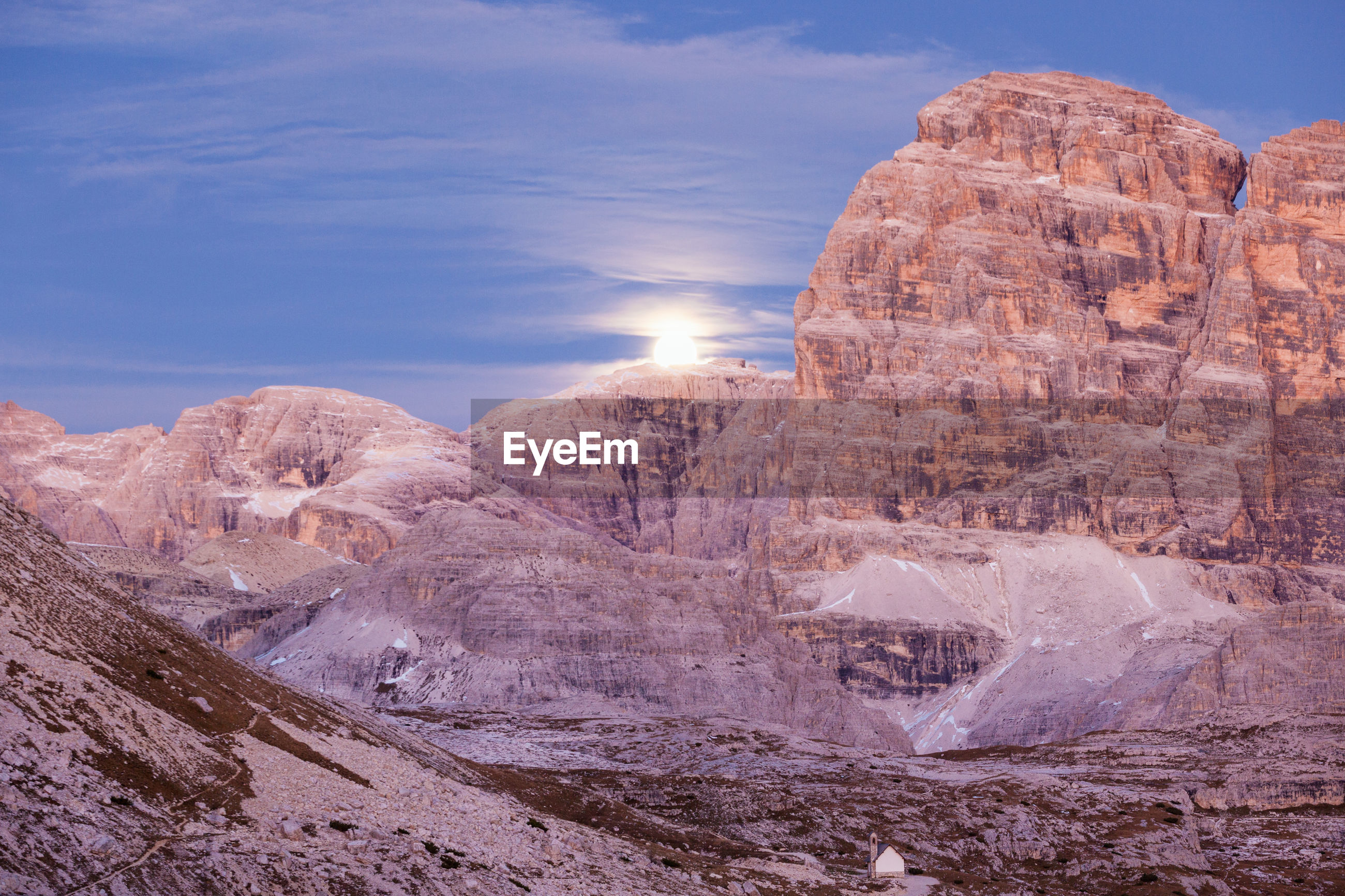 Moonrise over the mountains at sunset