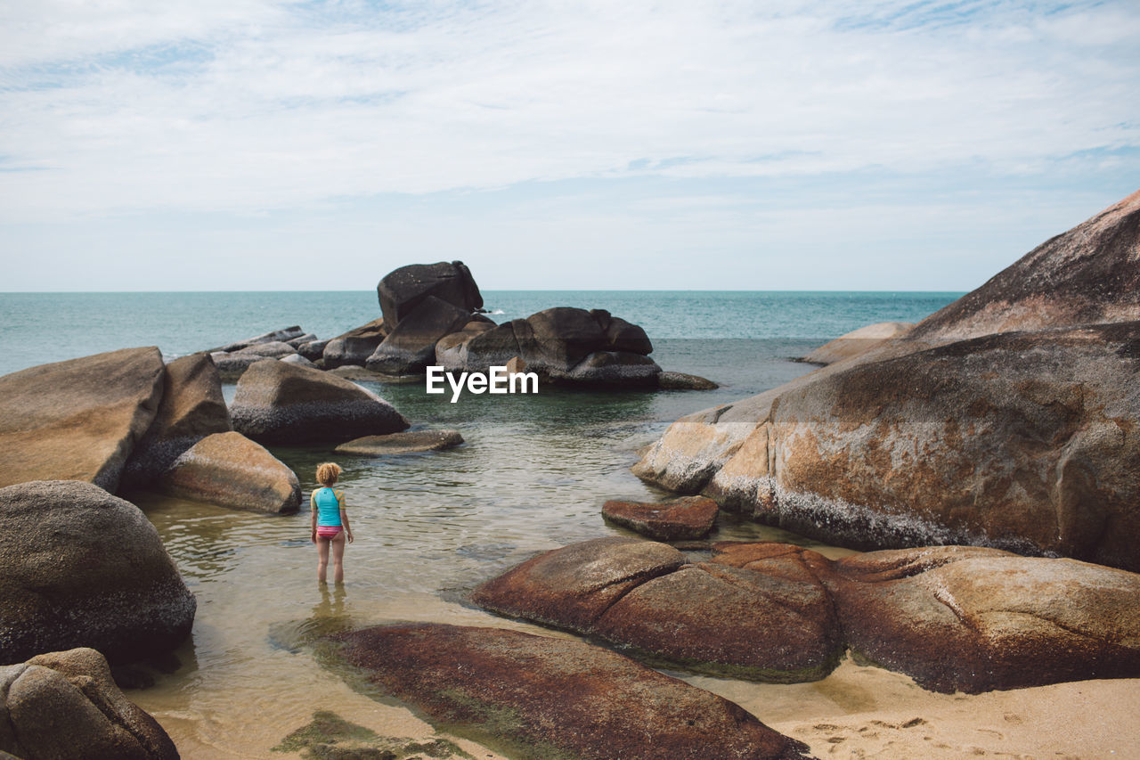 Woman Standing In Sea By Rocks Against Sky