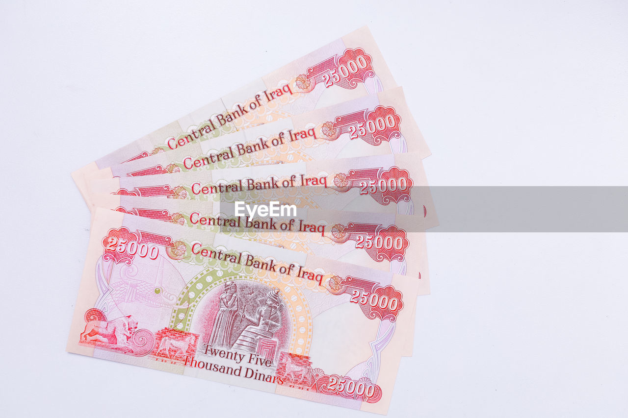 white background, studio shot, currency, indoors, finance, still life, business, close-up, wealth, no people, text, paper currency, cut out, communication, western script, high angle view, number, copy space, script, savings, economy, financial item