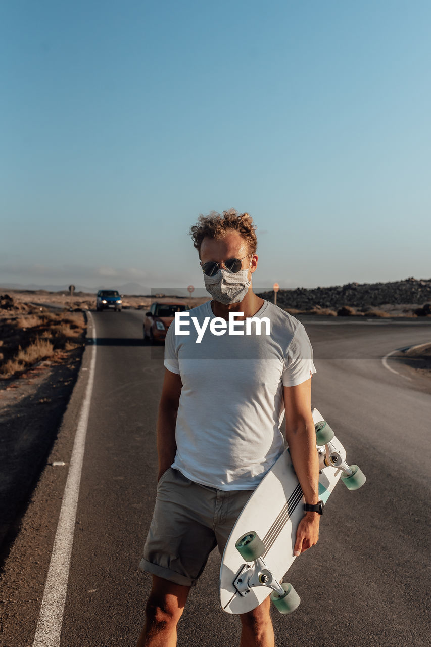 Portrait of man standing on road against clear sky with electric skateboard and mask