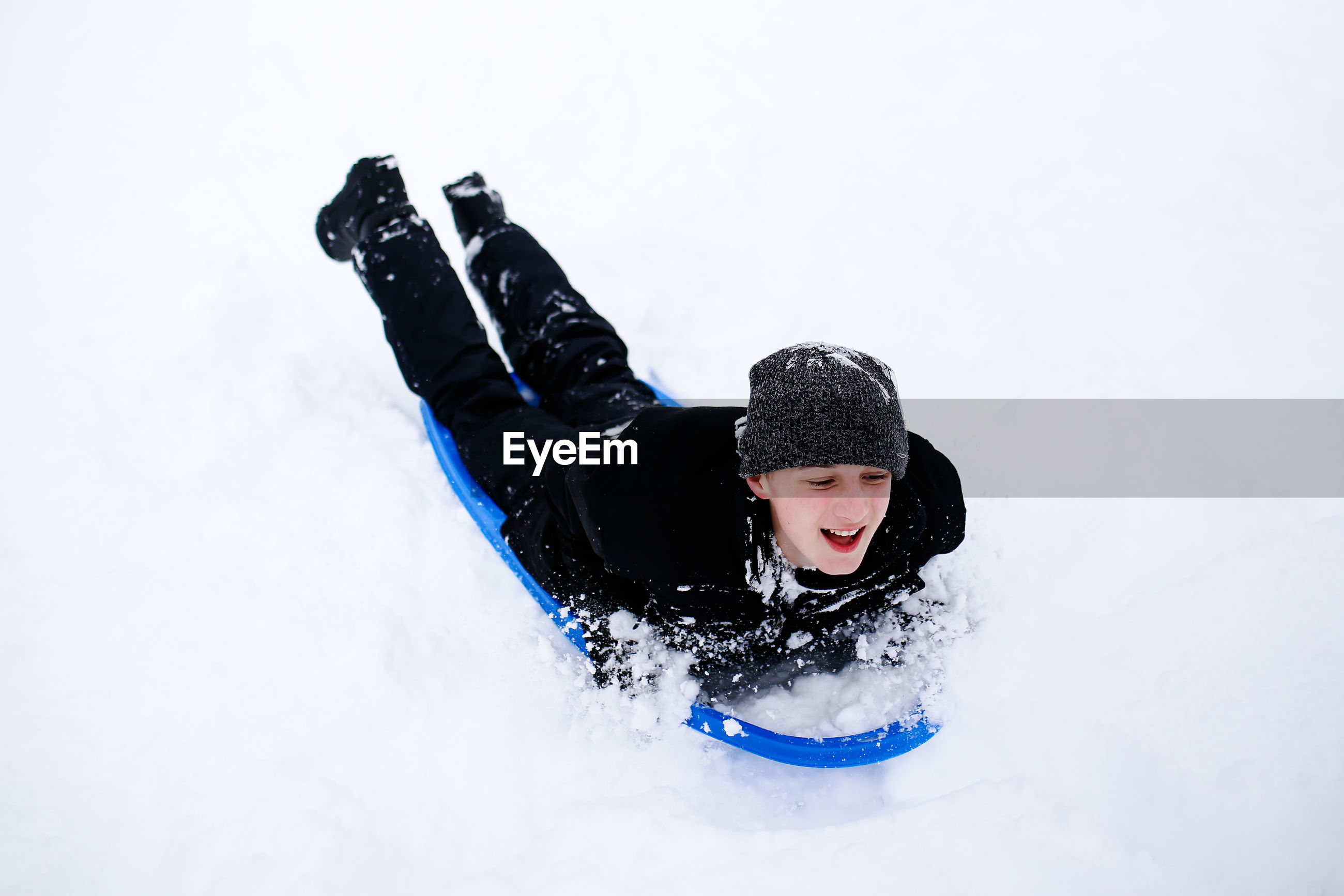 Full length of boy tobogganing on snow
