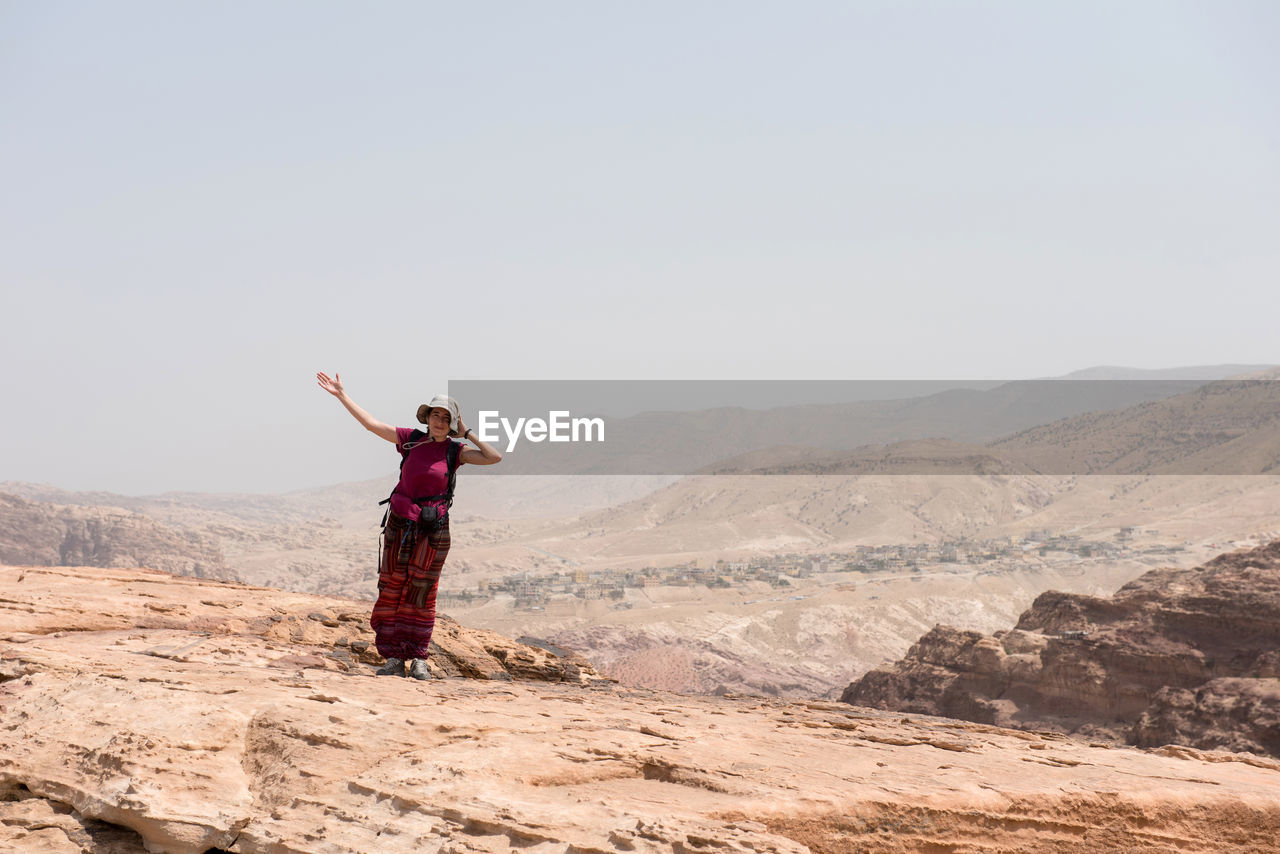 Full length of woman standing on mountain against clear sky
