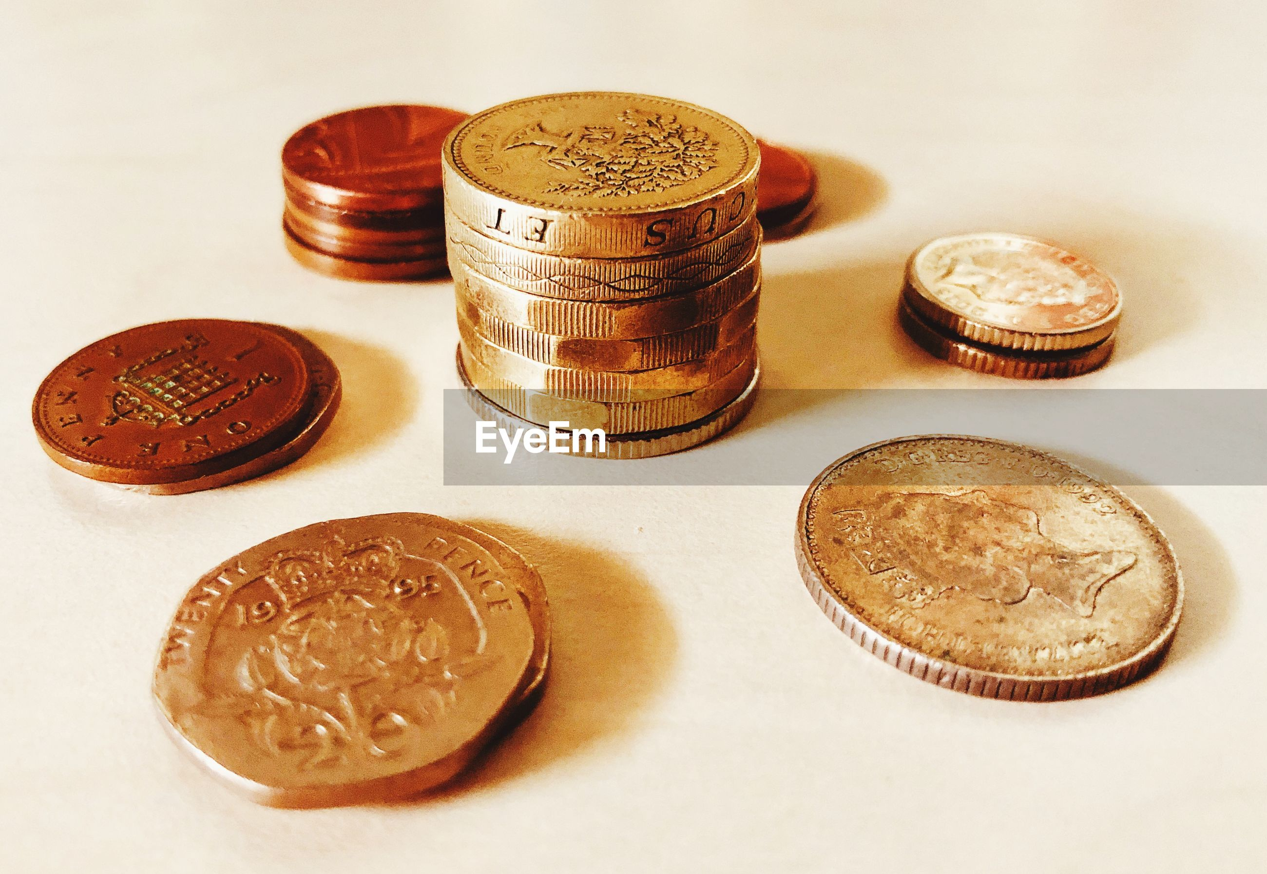 HIGH ANGLE VIEW OF COINS ON WHITE TABLE