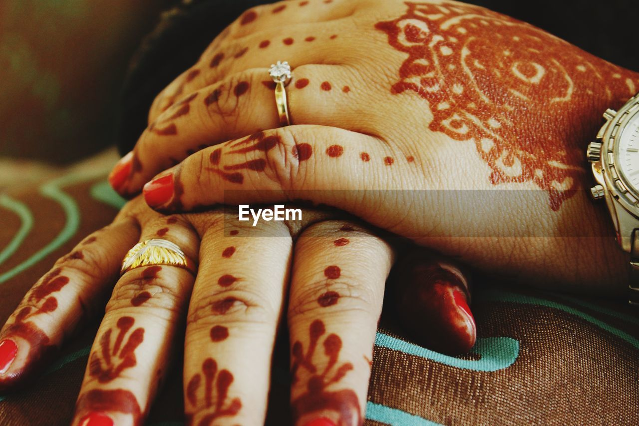 human hand, hand, human body part, indoors, body part, close-up, one person, real people, creativity, women, finger, human finger, focus on foreground, henna tattoo, tattoo, art and craft, lifestyles, adult, pattern, nail, human limb, floral pattern