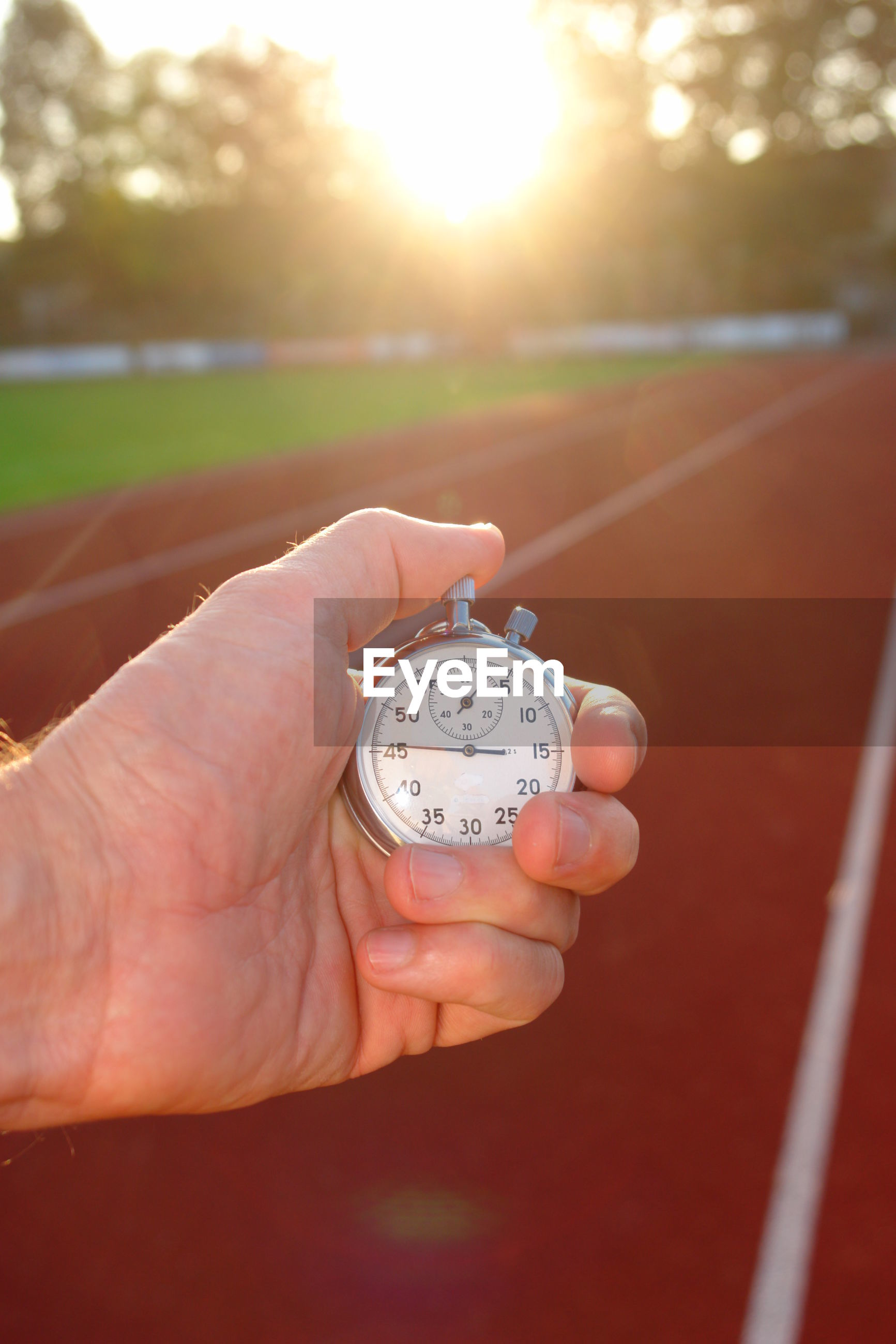 Close-up of hand holding stopwatch at running track