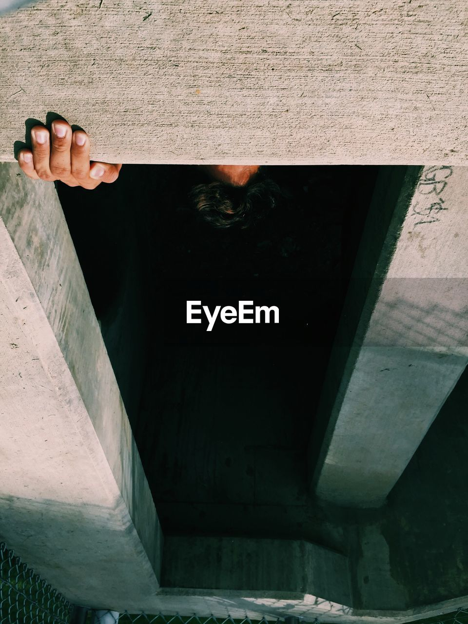 Upside Down Image Of Man Standing Behind Concrete Wall