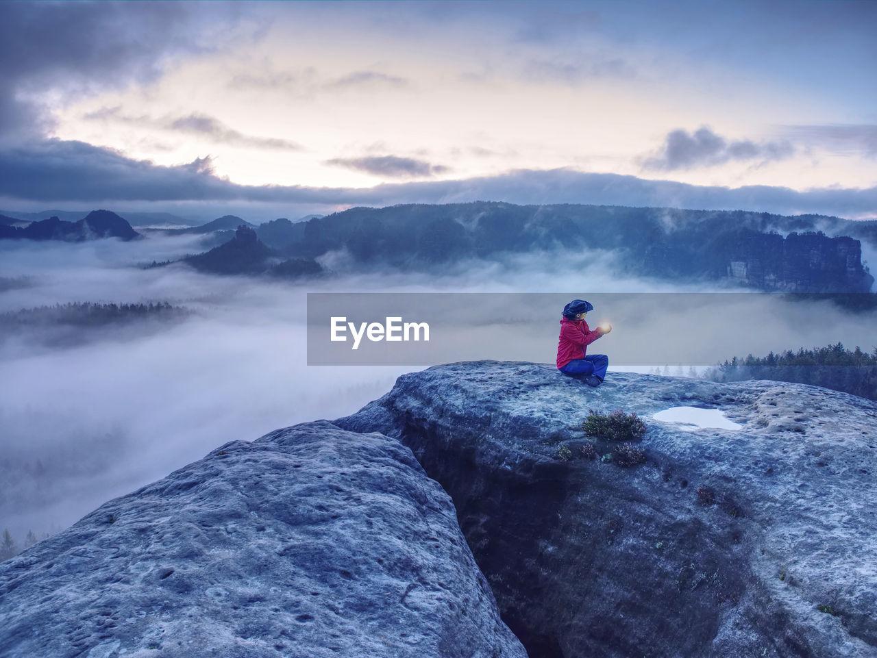 Woman holding lantern. girl alone sit on mountain summit likes ship in misty ocean. mysterious night