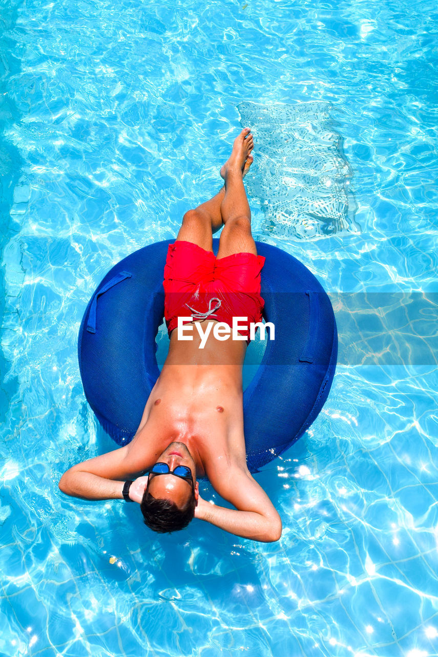 High angle view of shirtless man lying on inflatable ring in swimming pool