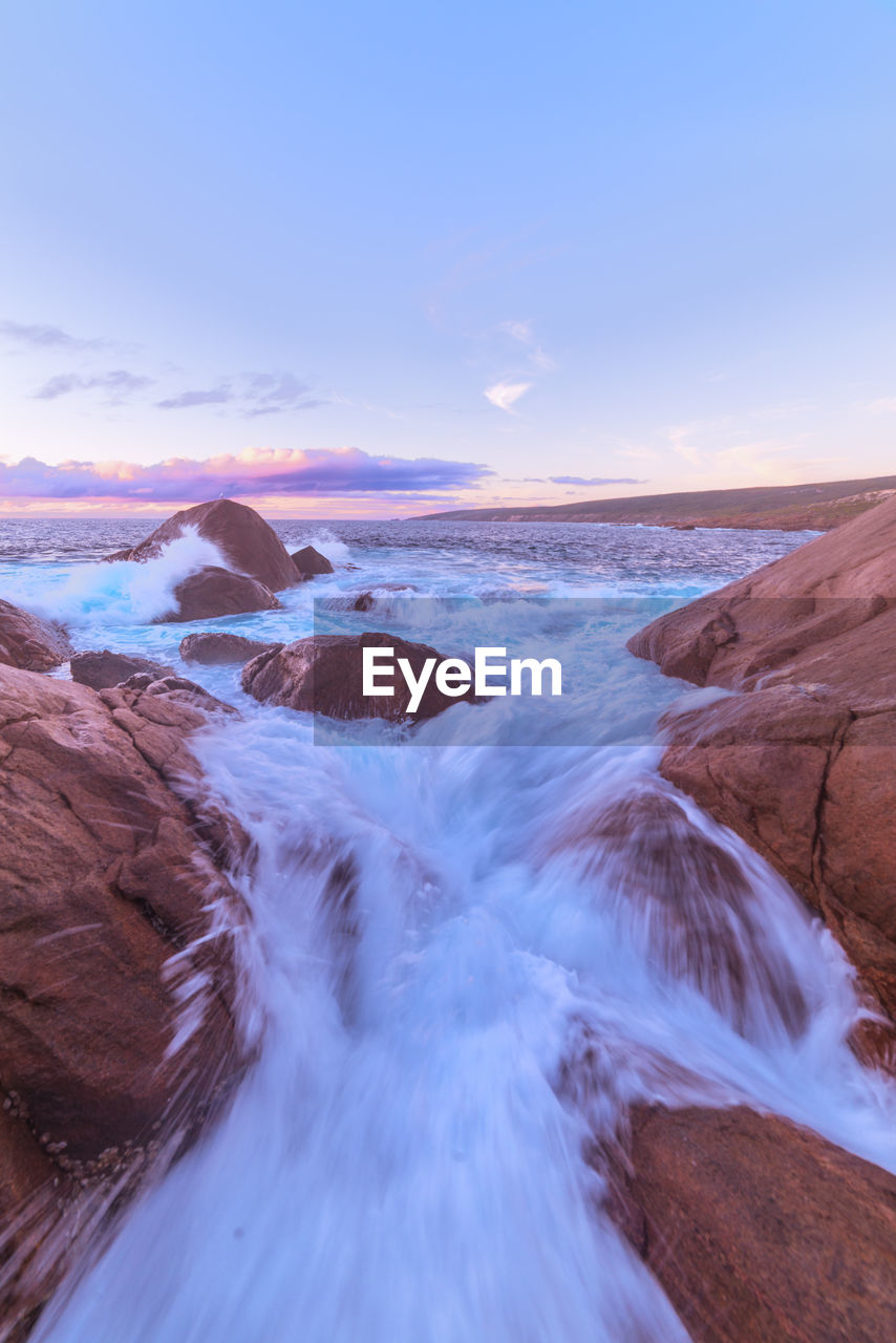 scenics - nature, water, sky, beauty in nature, sea, tranquil scene, sunset, non-urban scene, tranquility, nature, land, idyllic, no people, motion, beach, rock, remote, outdoors, rock - object, flowing water