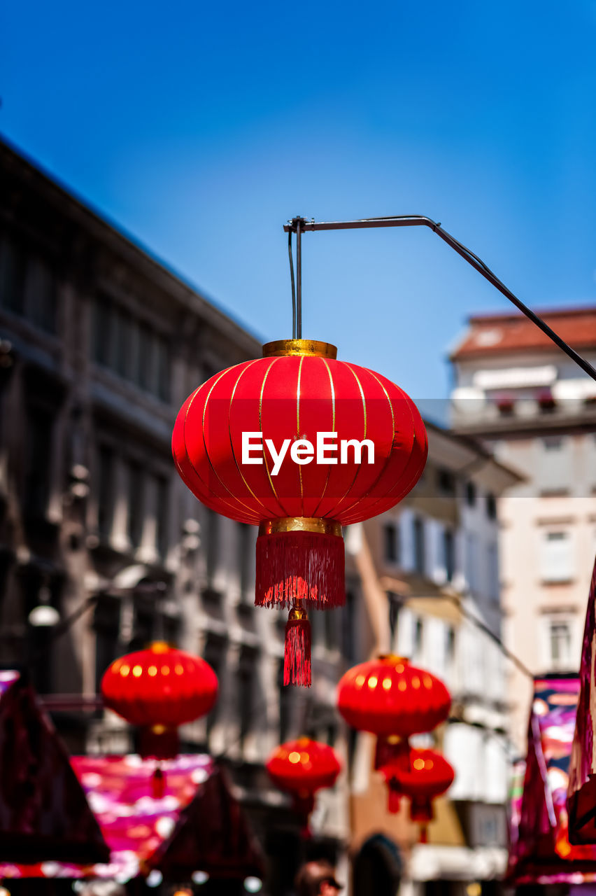 building exterior, red, lighting equipment, architecture, built structure, lantern, chinese lantern, focus on foreground, hanging, city, building, illuminated, sky, decoration, no people, day, low angle view, outdoors, festival