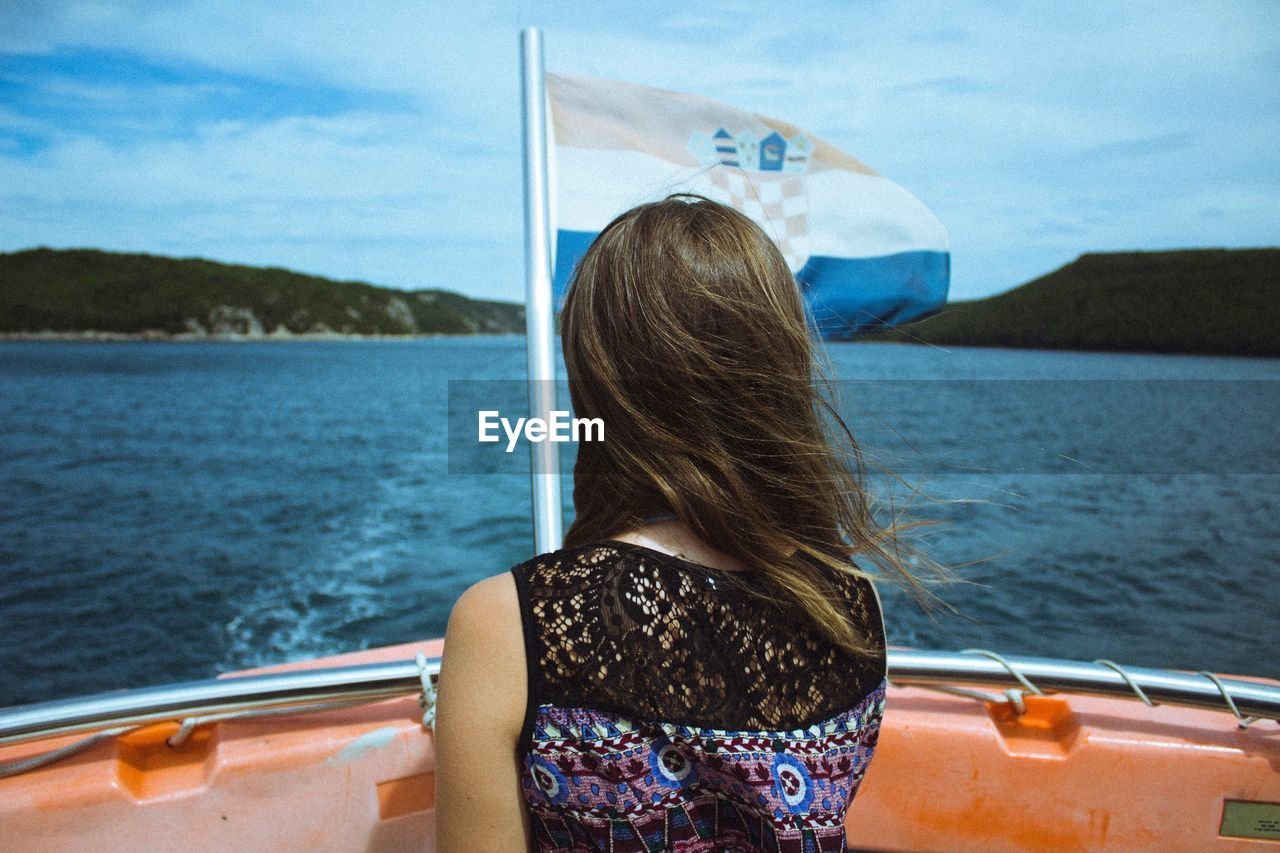 Rear View Of Woman By Croatian Flag In Boat On Lake