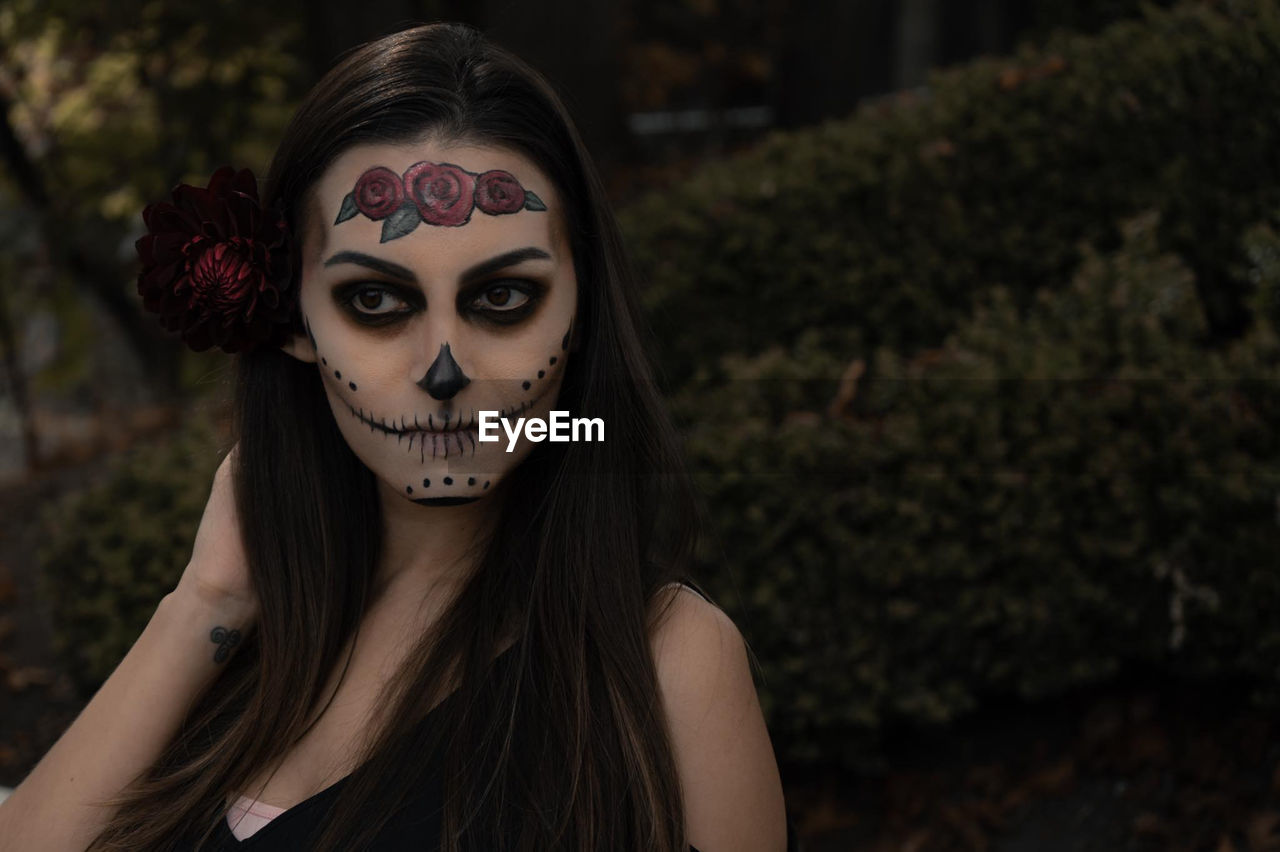 Close-up of thoughtful woman with spooky halloween make-up against plants