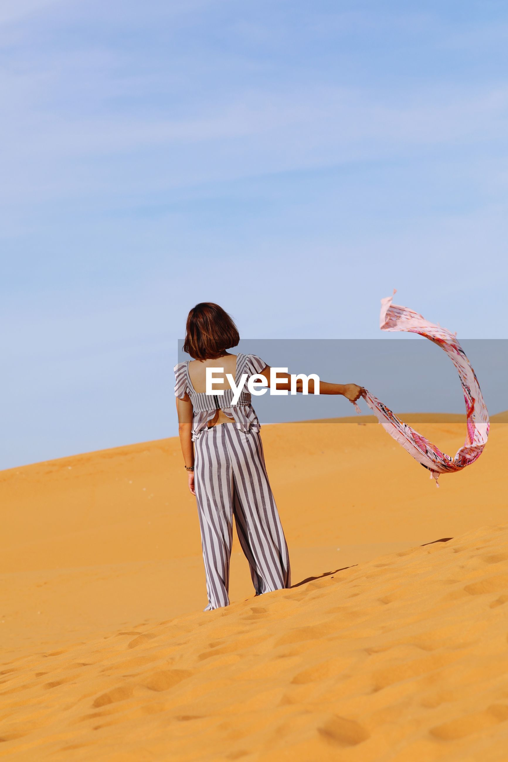 REAR VIEW OF WOMAN WITH UMBRELLA ON BEACH