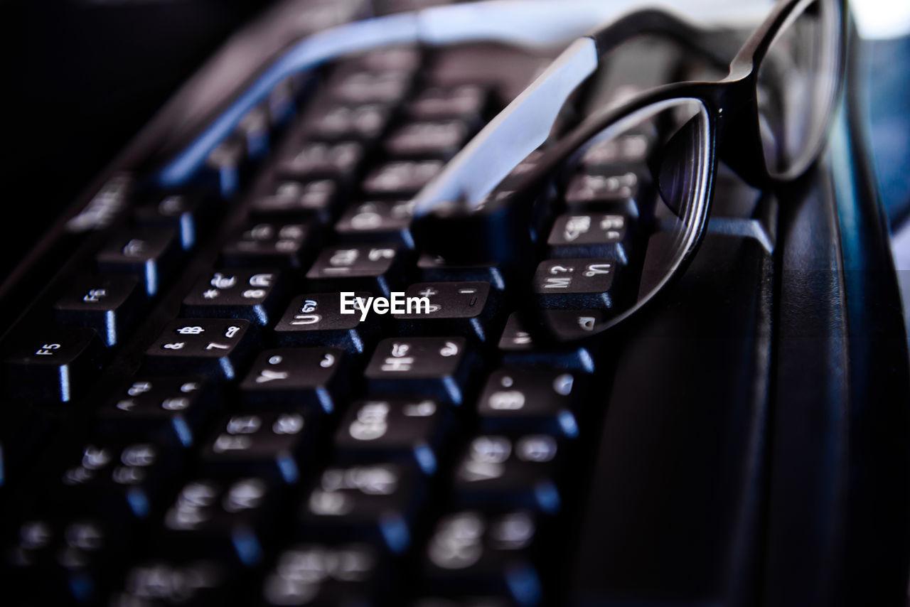 Close-Up Of Computer Keyboard And Eyeglasses