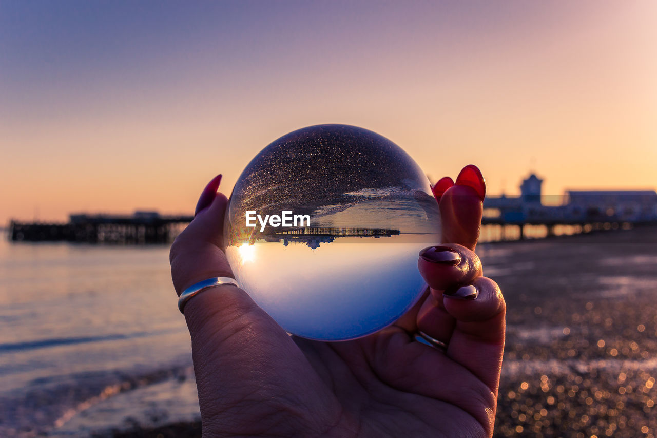 sky, holding, sunset, human hand, one person, hand, human body part, crystal ball, real people, focus on foreground, nature, sphere, personal perspective, architecture, building exterior, city, sunlight, close-up, built structure, unrecognizable person, body part, finger, outdoors, cityscape, lens flare