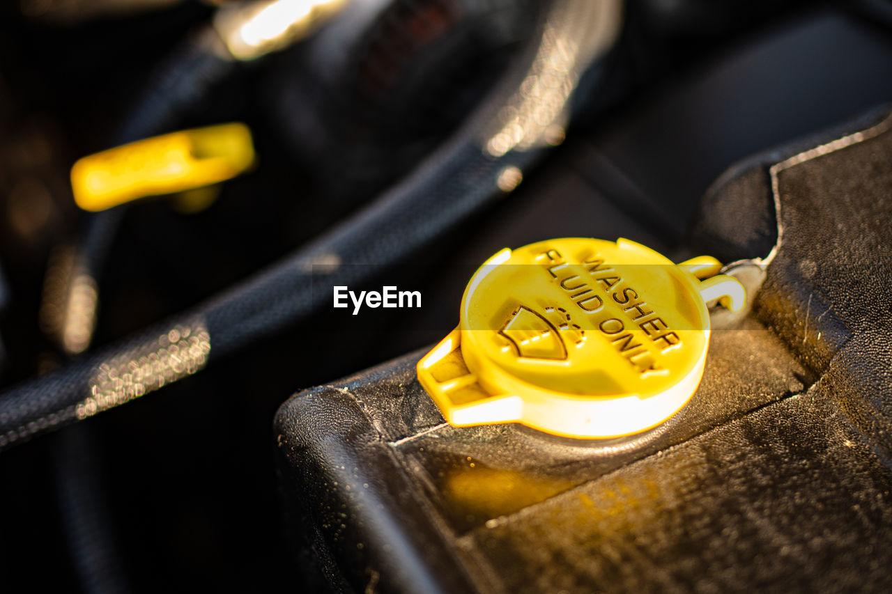 HIGH ANGLE VIEW OF YELLOW MACHINE ON METAL