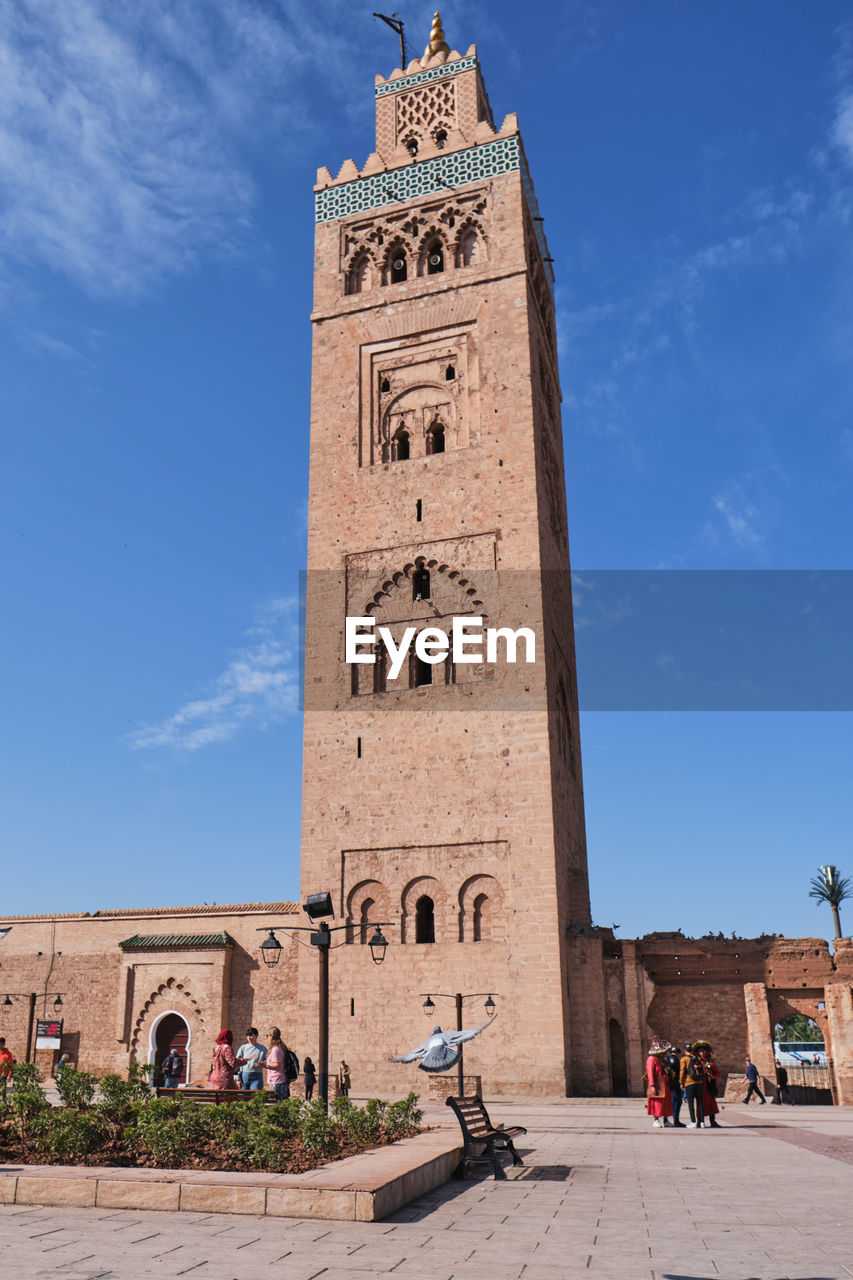 built structure, architecture, building exterior, sky, building, tower, blue, day, nature, the past, history, real people, travel destinations, low angle view, clock tower, religion, incidental people, tall - high, place of worship, travel, arch, outdoors, clock