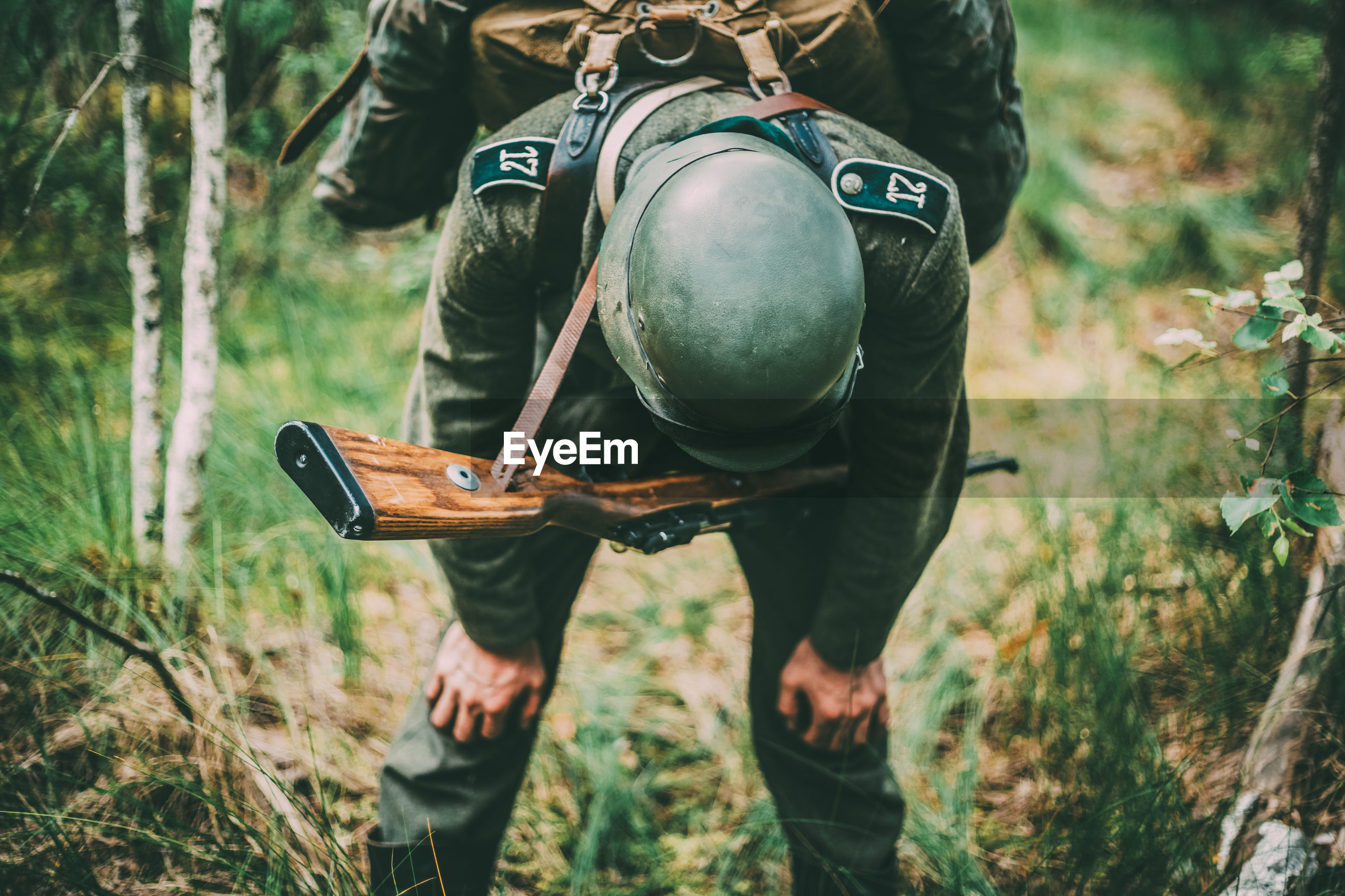 Tired soldier with rifle standing in forest
