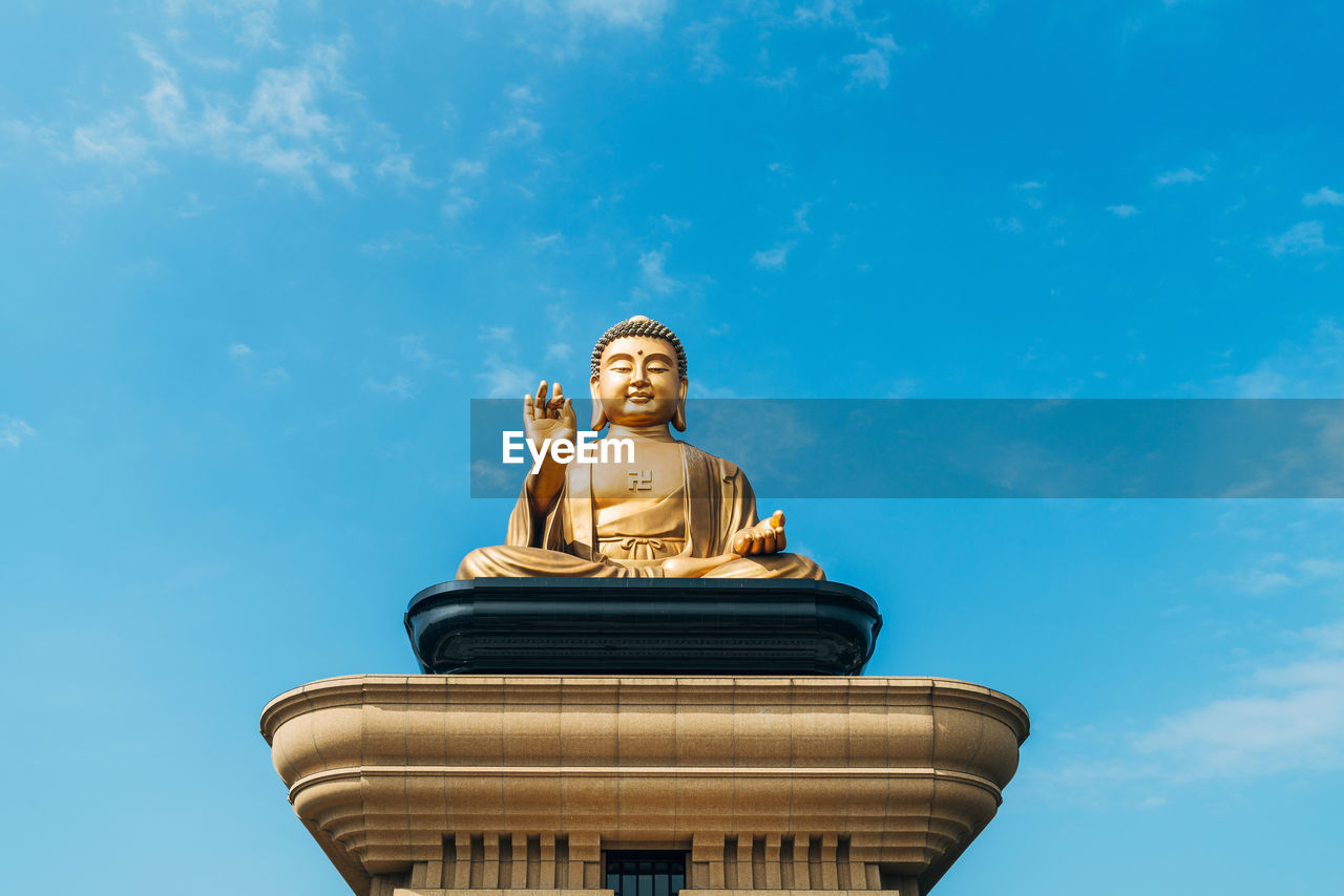 low angle view, human representation, sky, art and craft, representation, male likeness, sculpture, statue, blue, creativity, nature, architecture, no people, built structure, day, craft, gold colored, religion, cloud - sky, spirituality