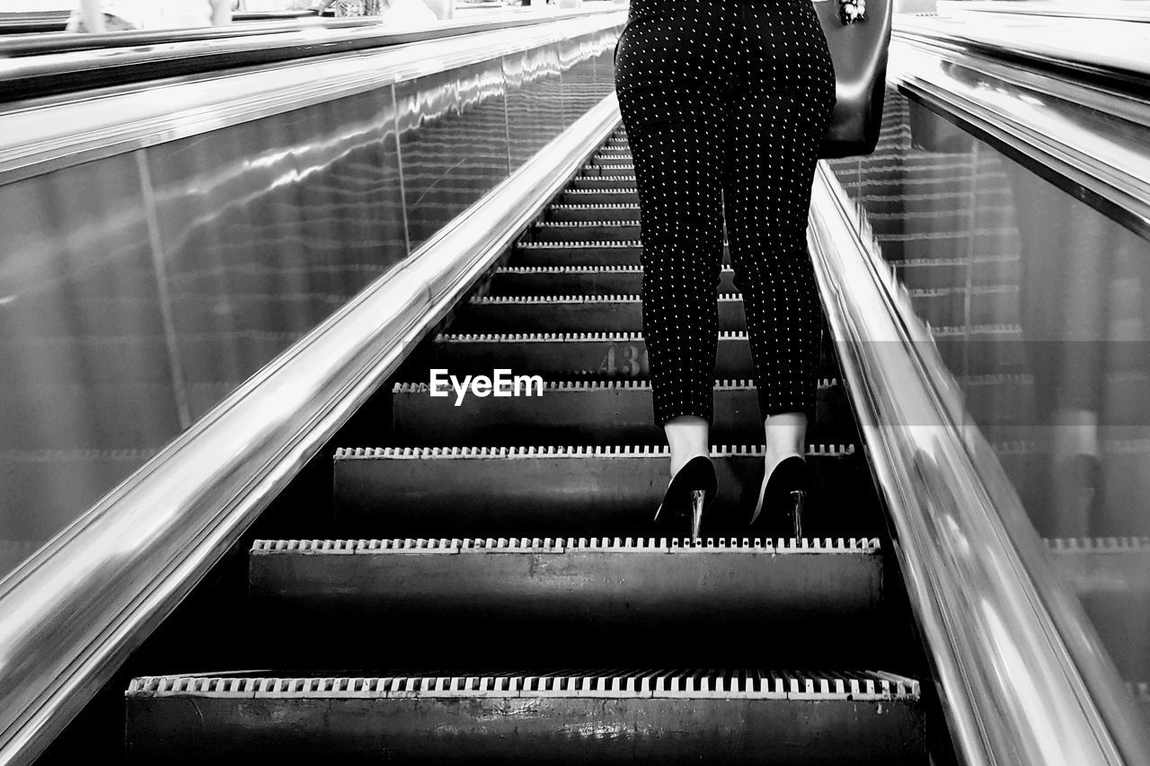 Low Angle View Of Woman Standing On Escalator