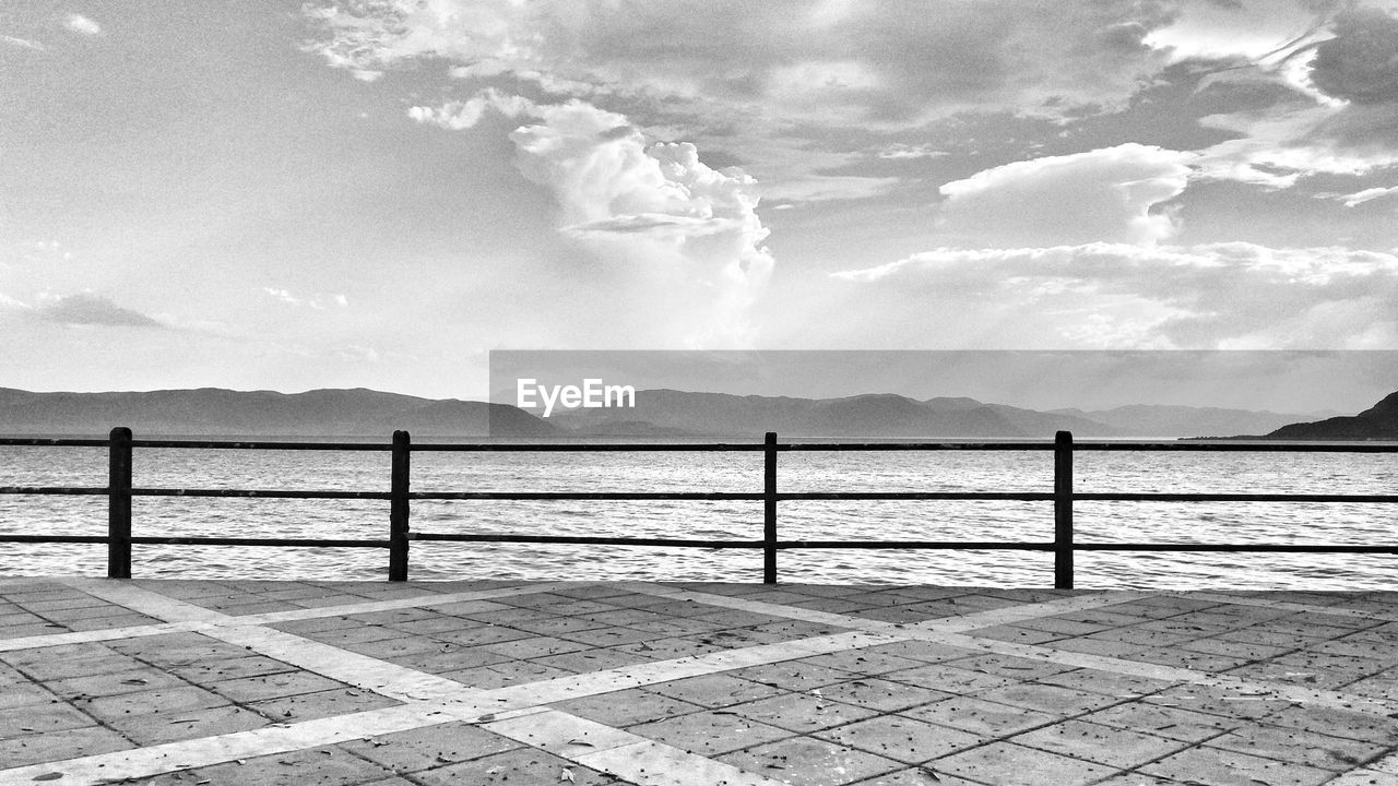 sky, cloud - sky, scenics - nature, water, beauty in nature, tranquil scene, nature, tranquility, mountain, railing, no people, day, sea, outdoors, idyllic, non-urban scene, mountain range, architecture, promenade, tiled floor