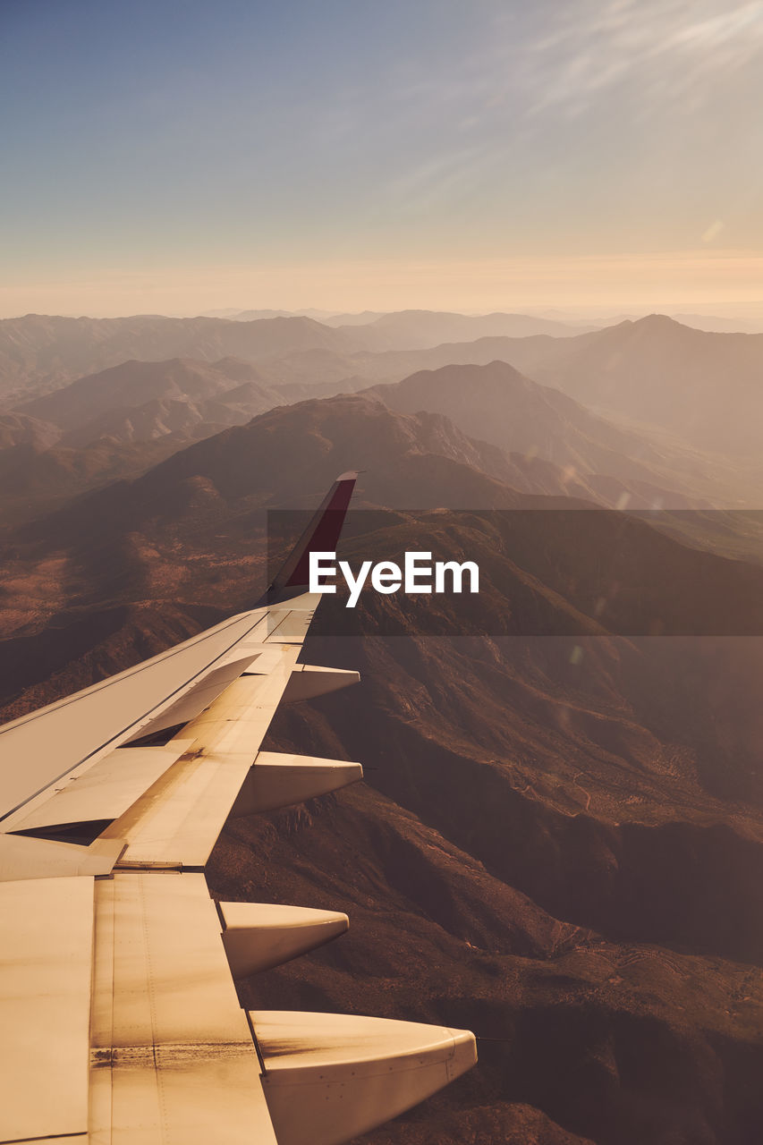 Scenic view of mountains against sky during sunset out of plane window