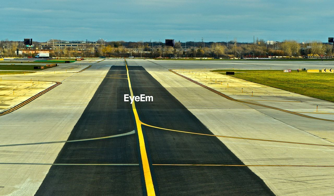 sky, architecture, built structure, no people, building exterior, nature, day, road marking, outdoors, symbol, marking, sign, airport, city, sport, direction, airport runway, empty, transportation, cloud - sky, dividing line