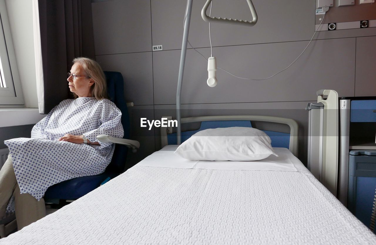 Senior Patient Sitting On Chair In Hospital