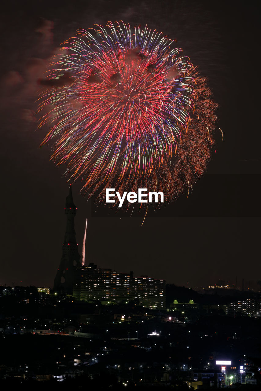 Low angle view of firework display over city at night