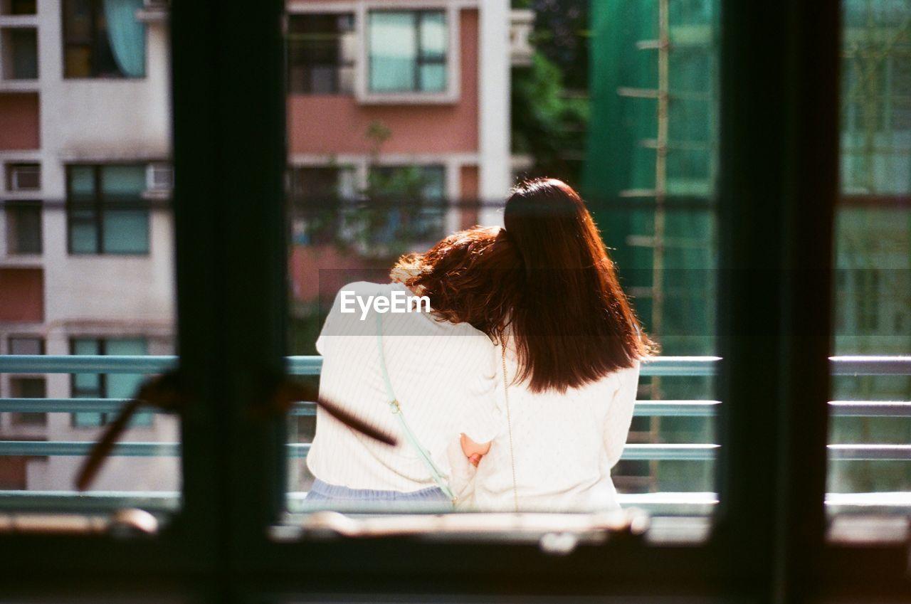 Rear view of women seen from window