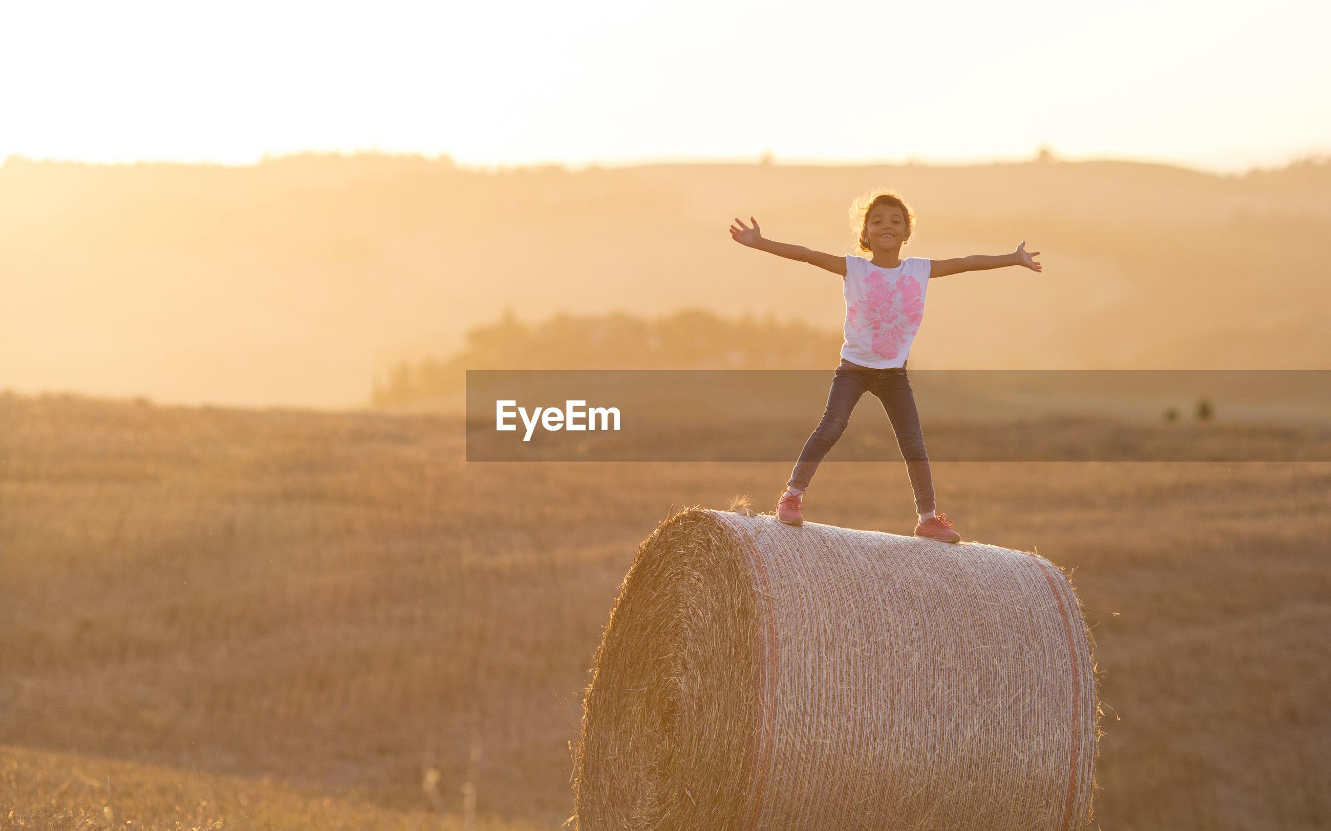 Full length of girl standing on hay bale