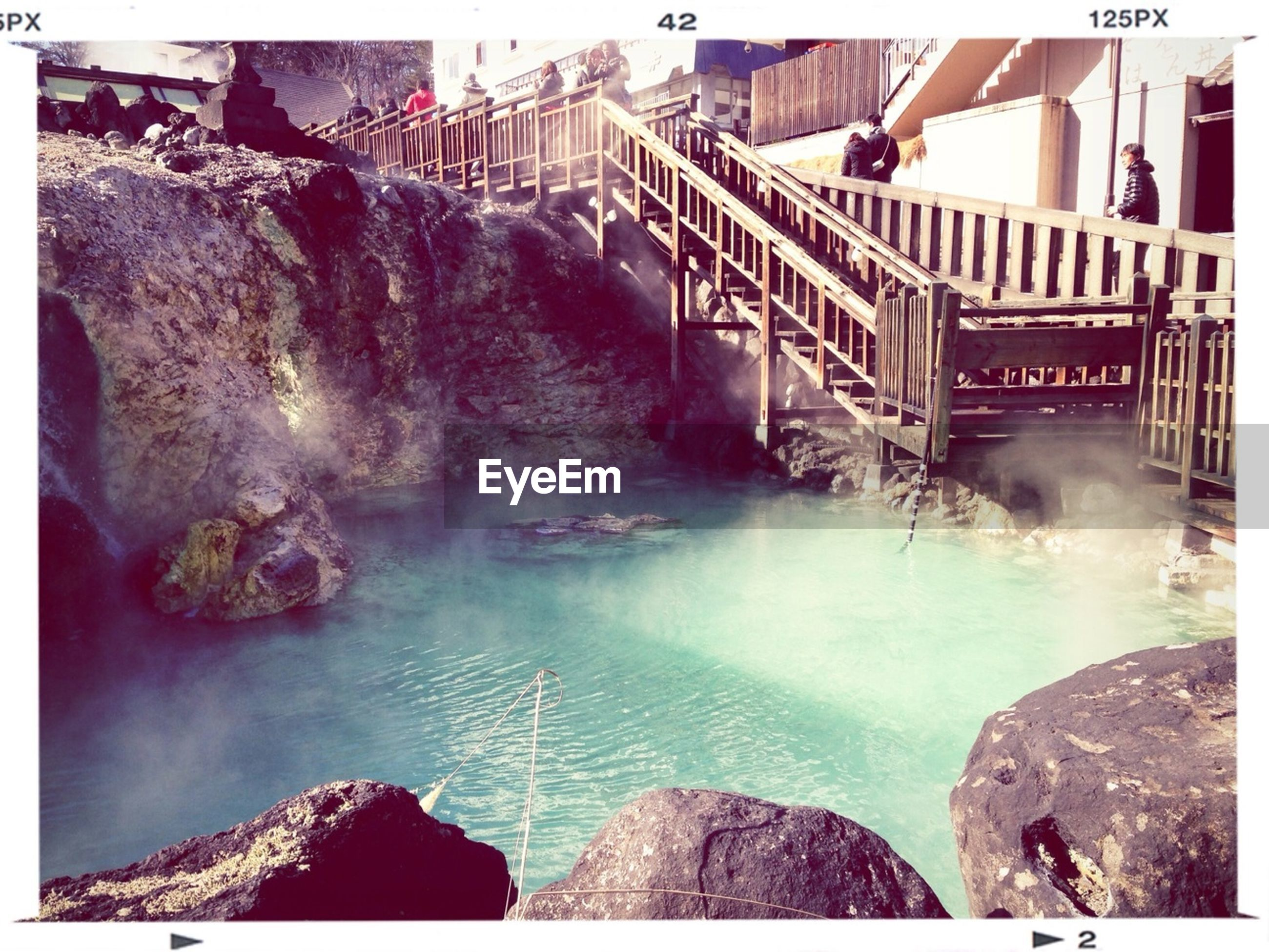 water, transfer print, rock - object, built structure, architecture, auto post production filter, connection, sea, bridge - man made structure, river, rock formation, waterfront, rock, nature, railing, day, outdoors, high angle view, no people, beauty in nature