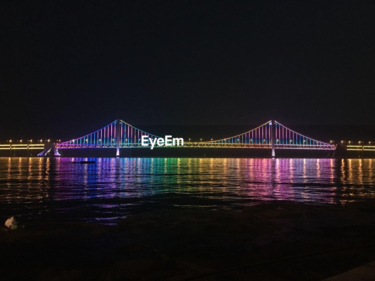 View Of Suspension Bridge Over River At Night