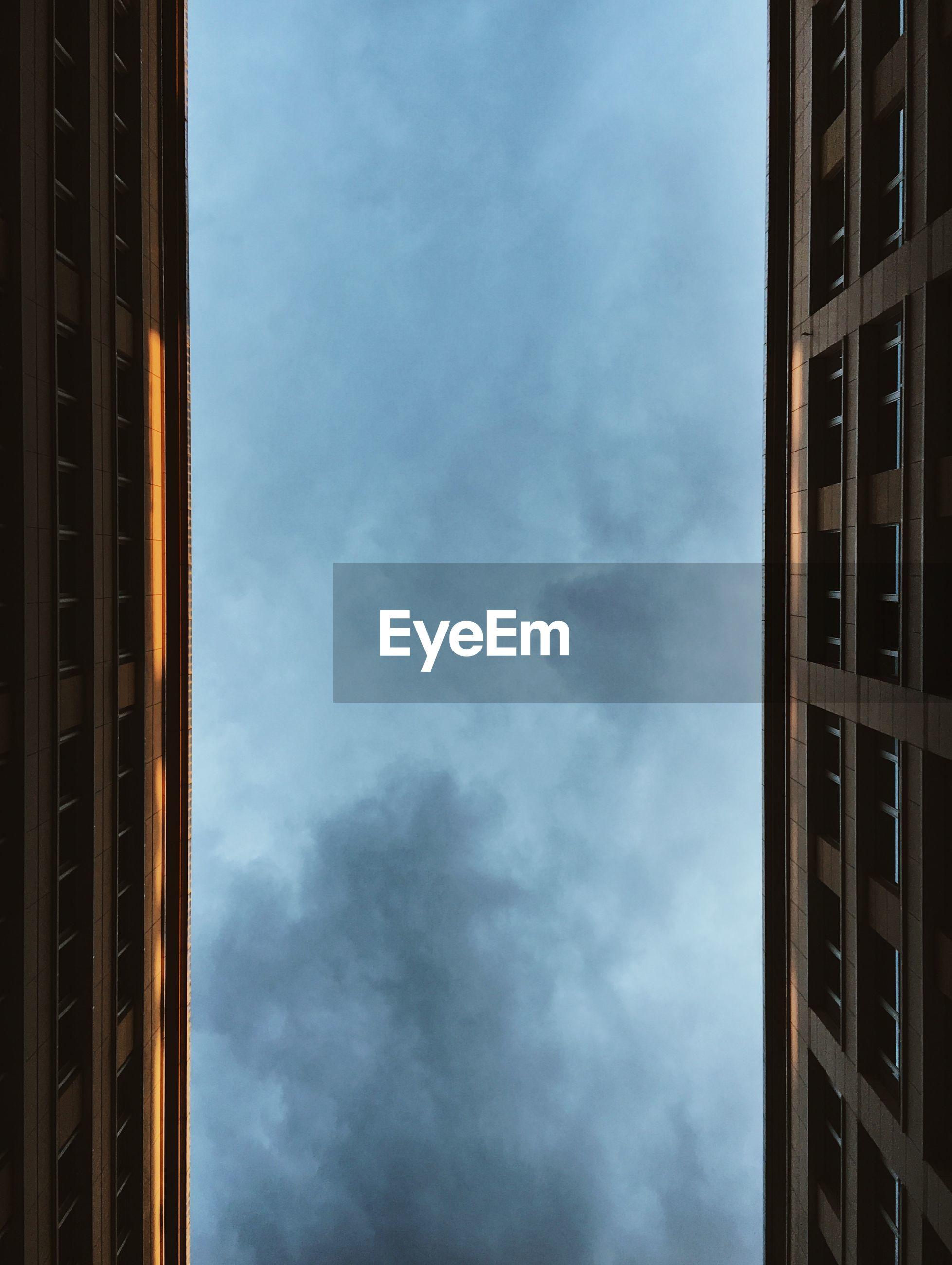 Directly below view of buildings against sky at dusk