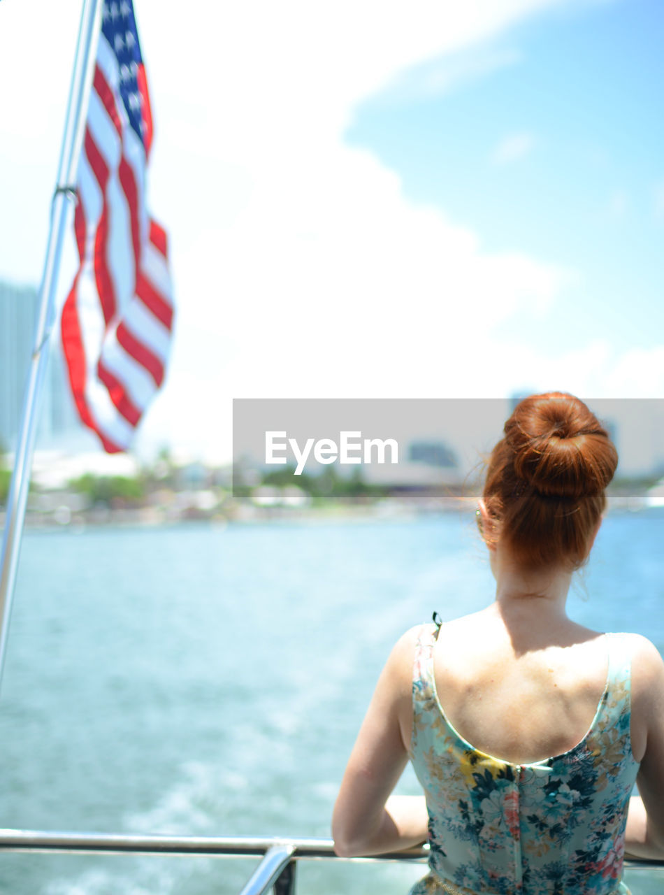 Rear View Of Woman Looking At Sea While Traveling On Boat With Flag