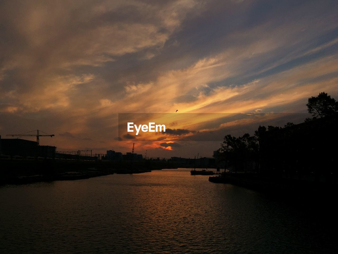 sunset, silhouette, water, sky, waterfront, river, no people, beauty in nature, nature, dusk, cloud - sky, outdoors, tranquility, scenics, architecture, city