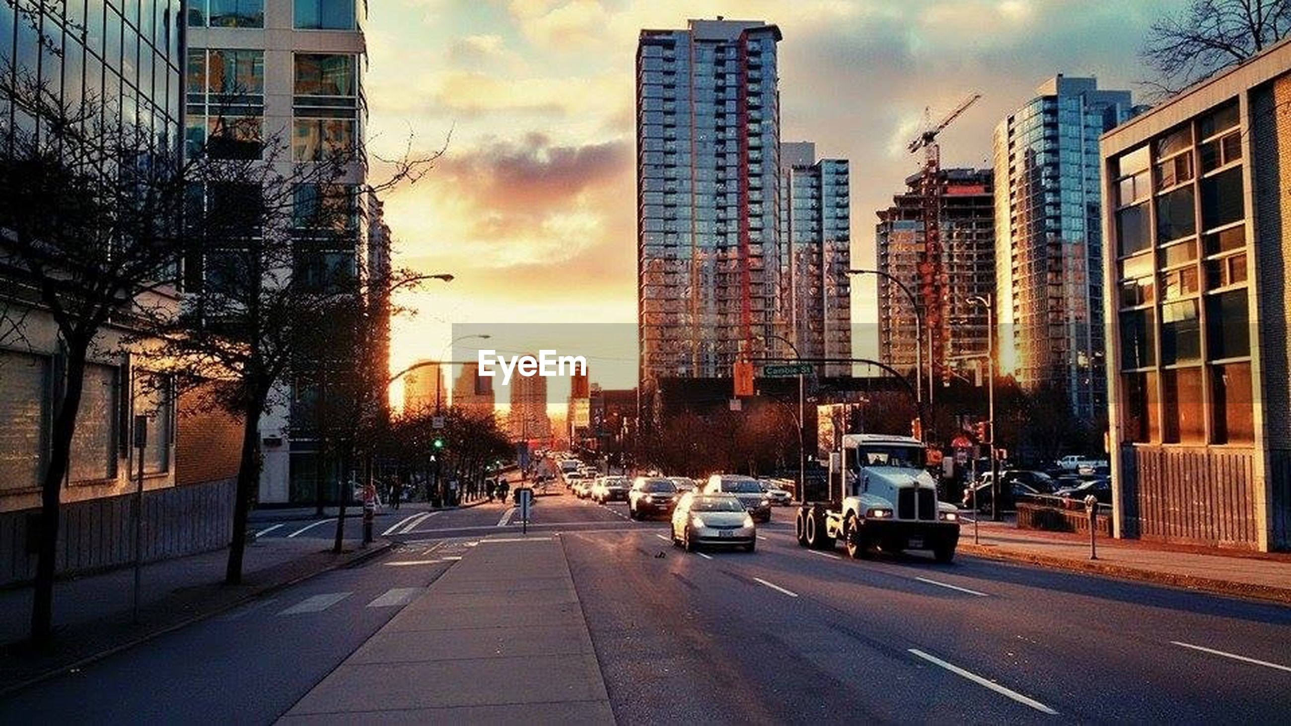 building exterior, architecture, built structure, city, transportation, car, street, land vehicle, sky, road, mode of transport, the way forward, sunset, building, city street, city life, cloud - sky, diminishing perspective, residential building, skyscraper