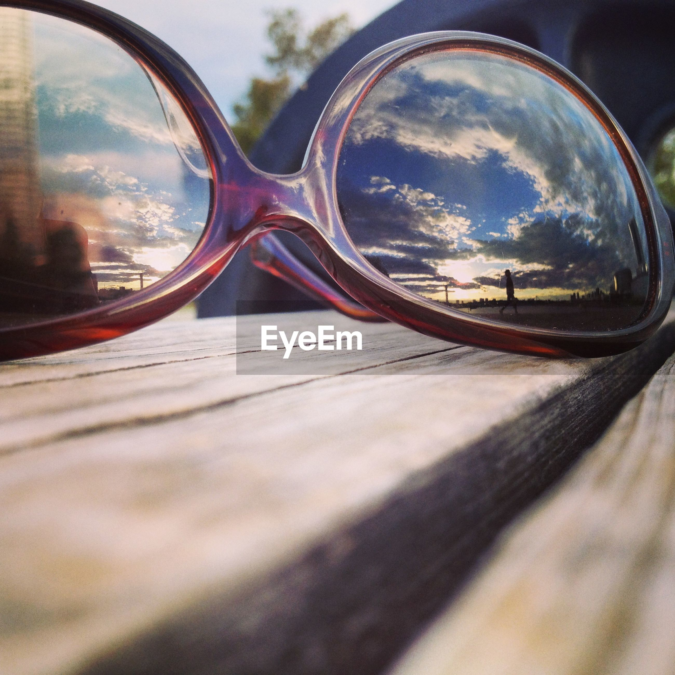 Cloudy sky reflected in sunglasses on wooden table