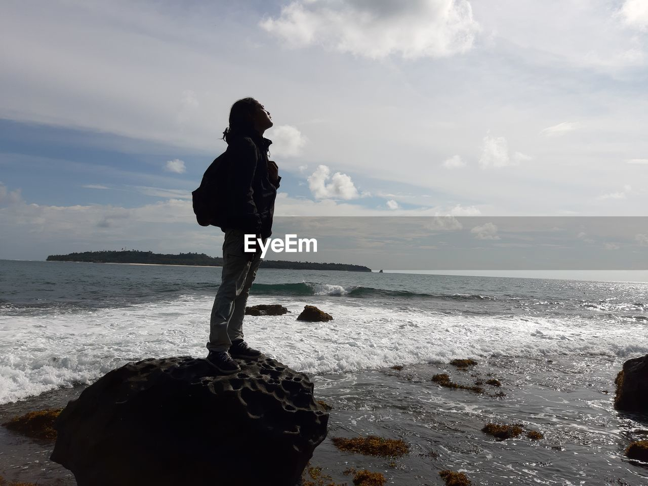 Young man standing on rock at beach